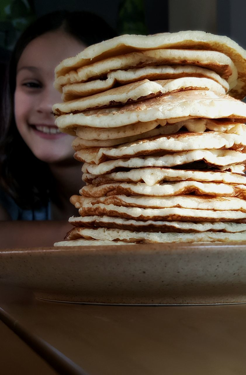Close-Up Of Pancakes Stacked In Plate With Girl In Background