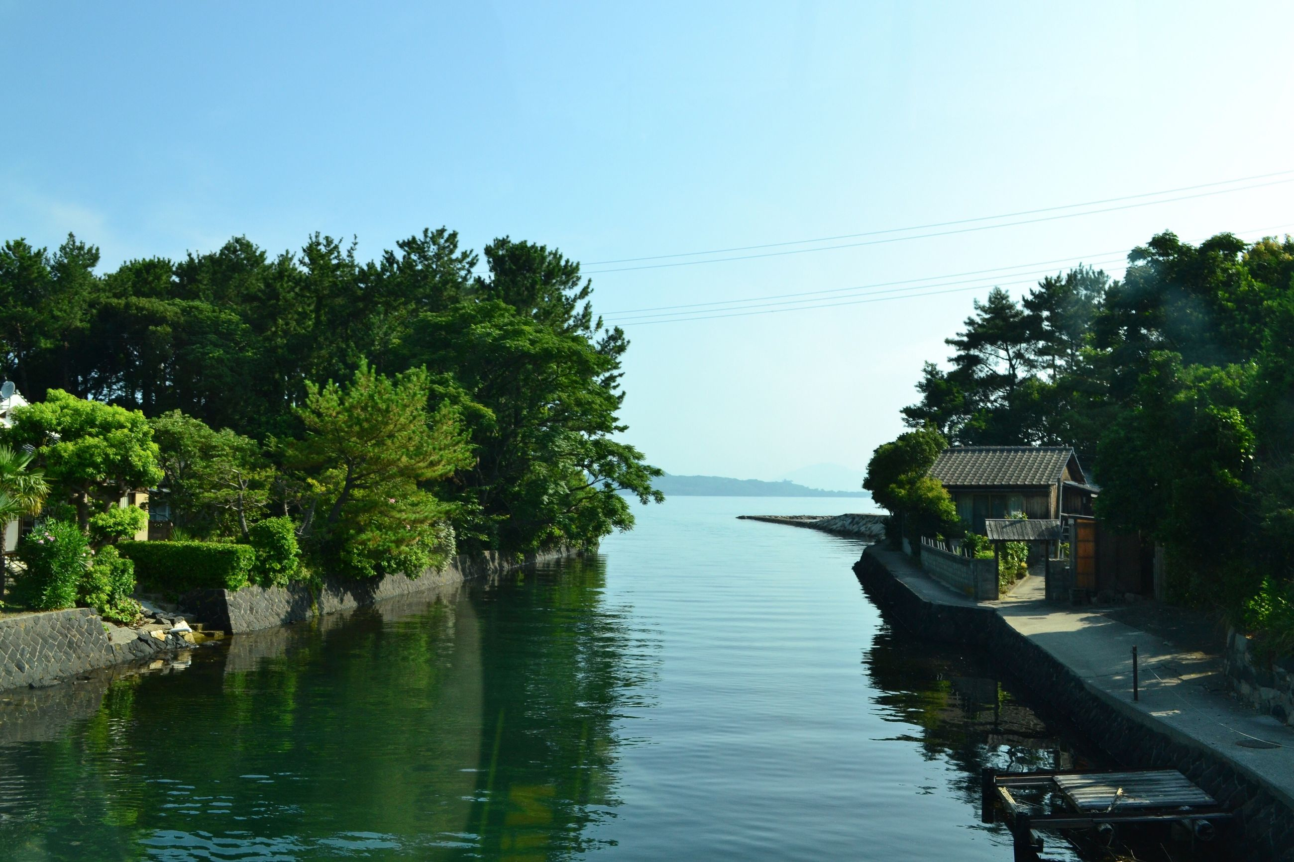 water, tree, clear sky, tranquil scene, scenics, river, architecture, tranquility, building exterior, sea, calm, blue, waterfront, growth, day, nature, beauty in nature, outdoors, riverbank, canal, no people, tourism, in front of, town, lakeside, remote