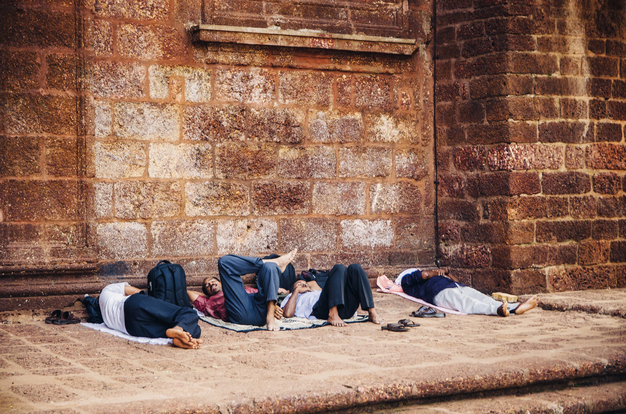 brick wall, sleeping, men, sitting, real people, outdoors, only men, day, adult, building exterior, architecture, young adult, city, adults only, people