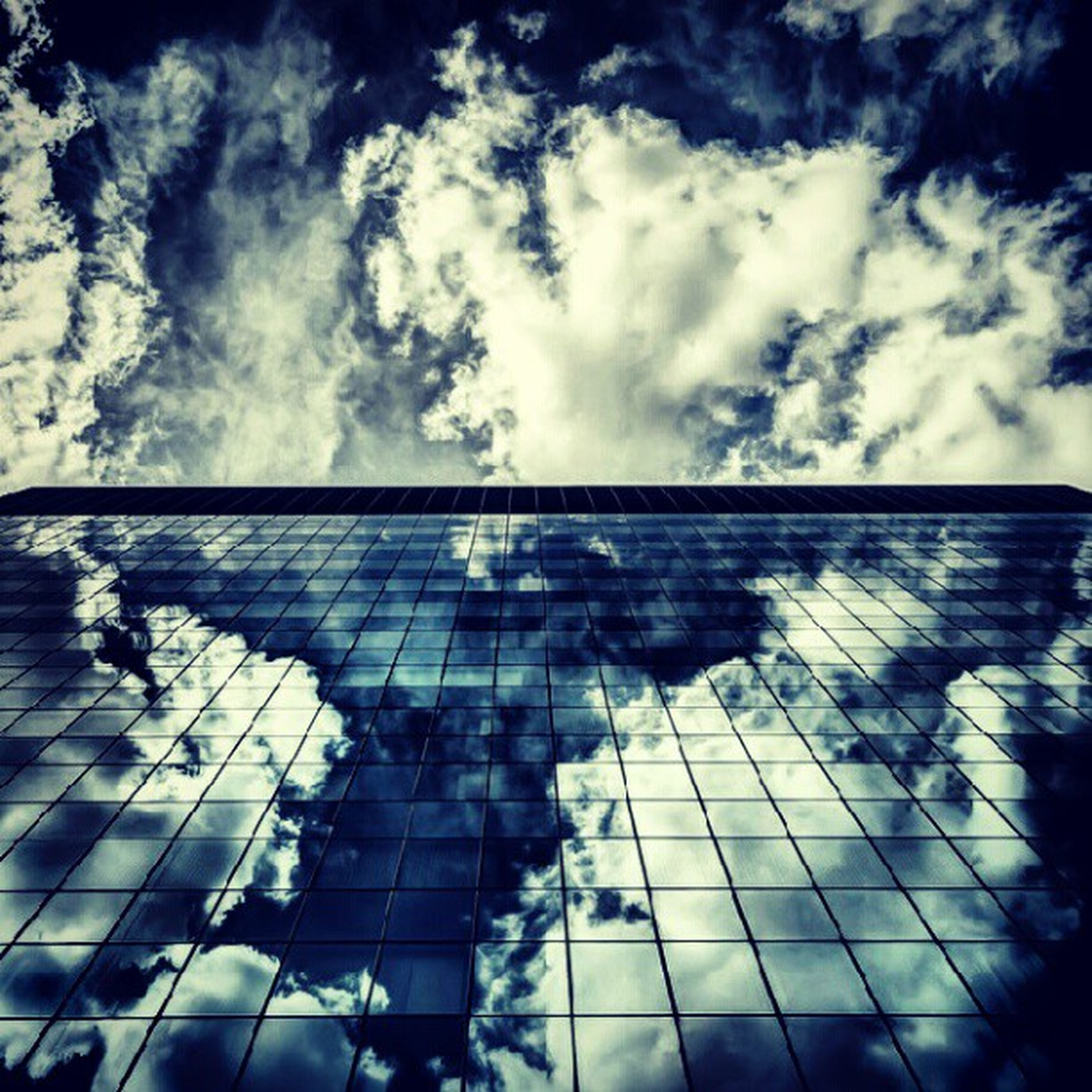 sky, cloud - sky, architecture, built structure, building exterior, low angle view, cloudy, cloud, reflection, pattern, glass - material, day, building, sunlight, outdoors, window, no people, wall - building feature, modern, weather