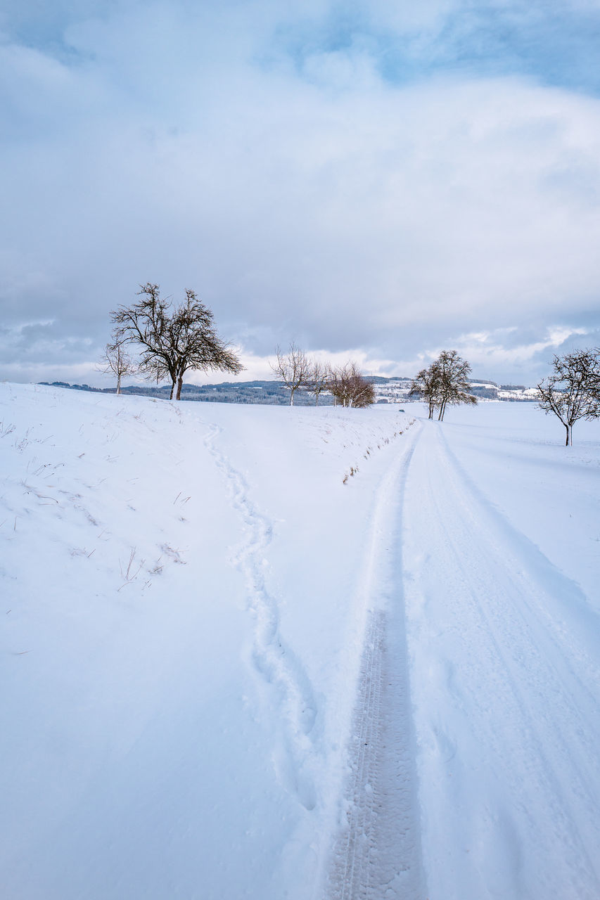 Scenic View Of Snow Covered Landscape Against Cloudy Sky At Knutwil
