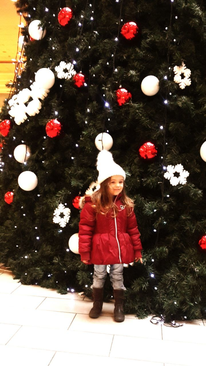 christmas, one person, childhood, christmas tree, real people, tree, casual clothing, celebration, christmas decoration, girls, full length, front view, christmas ornament, standing, lifestyles, indoors, illuminated, children only, day, bubble wand, people