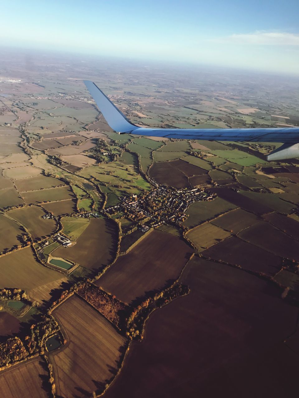 aerial view, landscape, airplane, transportation, scenics, tranquil scene, nature, outdoors, beauty in nature, journey, day, no people, aircraft wing, tranquility, sky, air vehicle, patchwork landscape, flying, airplane wing, sea, water, view into land