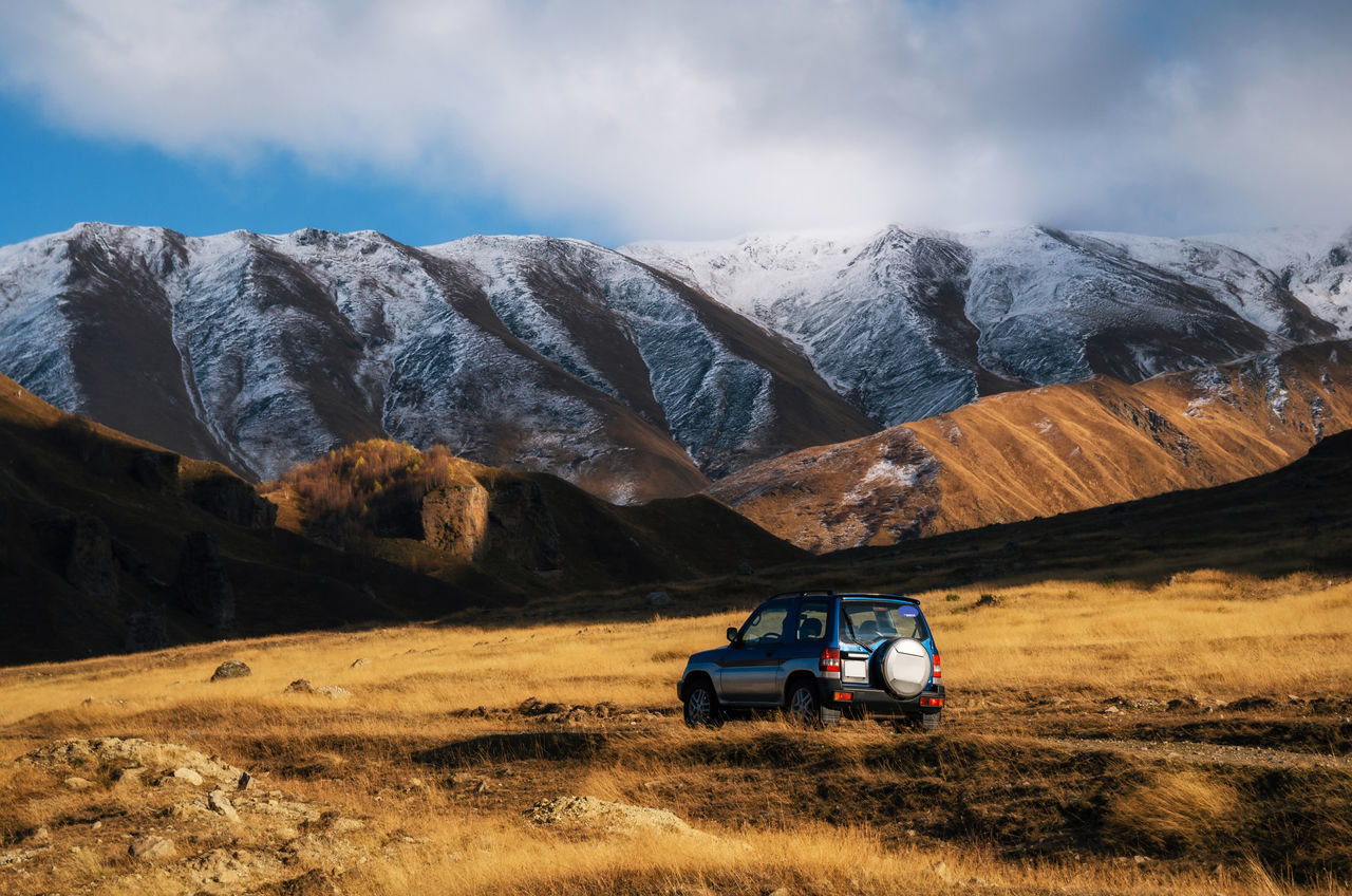 Off-road travel by the car on a mountain road against the rocks and the glacier in Caucasus, Georgia. Beautiful lights and colors at sunset. Adventure and traveling concept Adventure Adventure Club Beauty In Nature Cars Drive Extreme Terrain Land Vehicle Landscape Mountain Mountain Range Mountain Road Nature Offroad Outdoors Scenics Snow Tourism Tourist Attraction  Transportation Travel Traveling Travelling