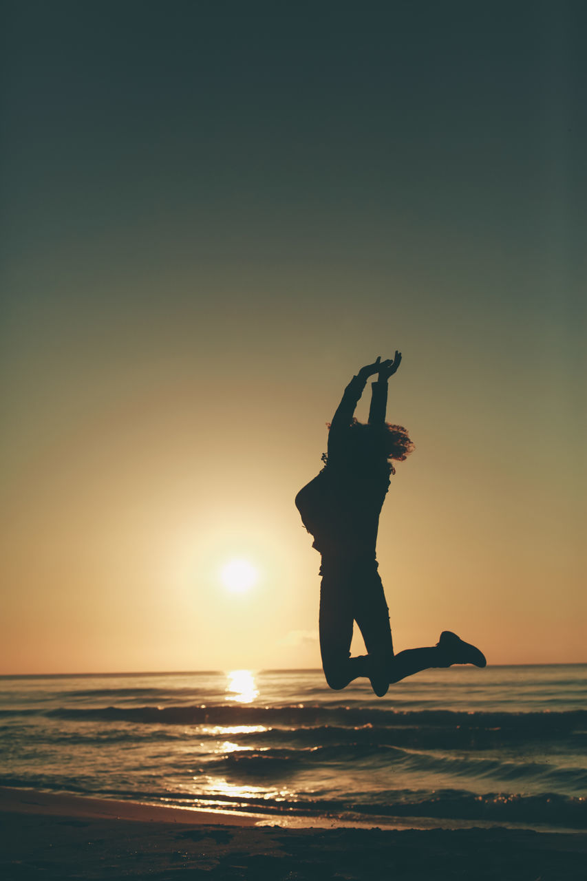 Full Length Of Silhouette Woman Jumping At Beach Against Sky During Sunset