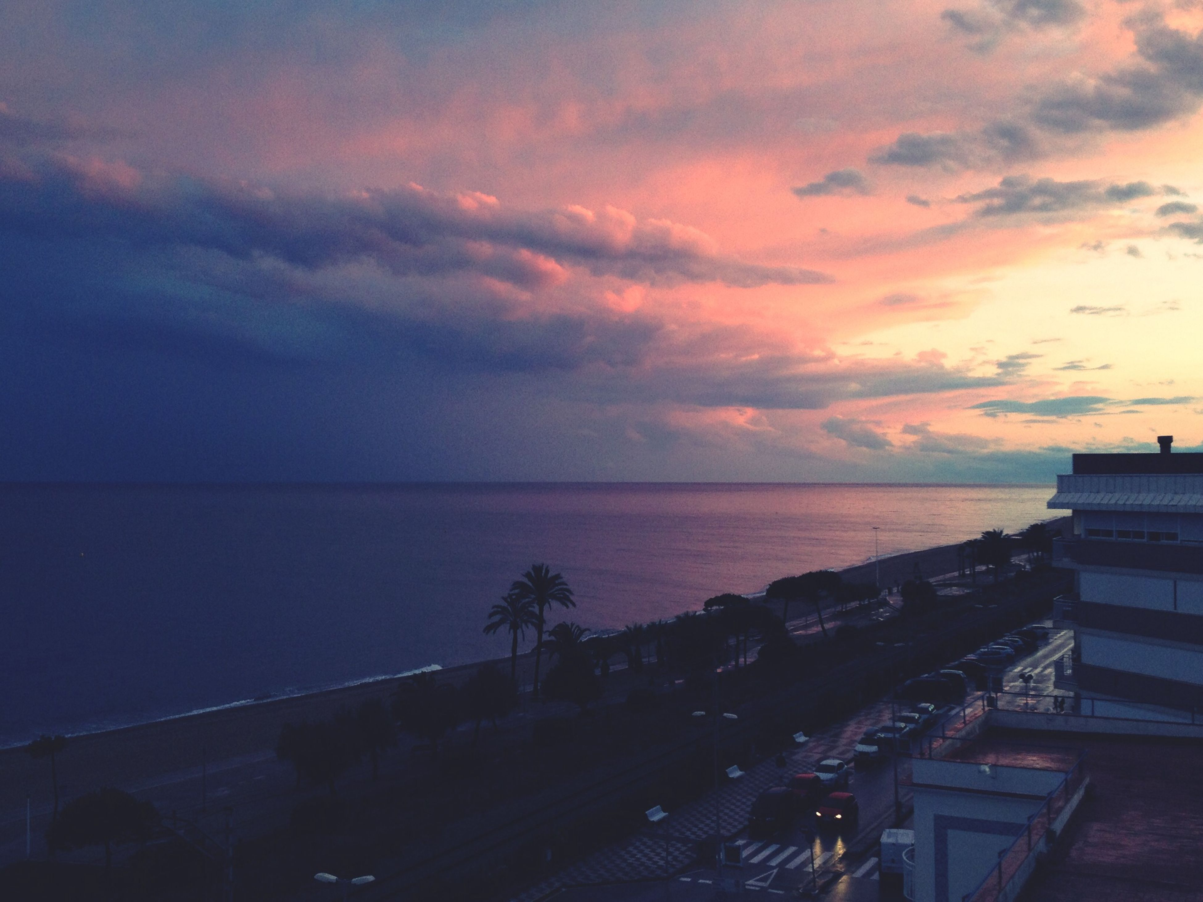 sea, horizon over water, sky, sunset, water, cloud - sky, scenics, beauty in nature, tranquil scene, tranquility, built structure, nature, architecture, idyllic, cloudy, cloud, building exterior, orange color, beach, railing
