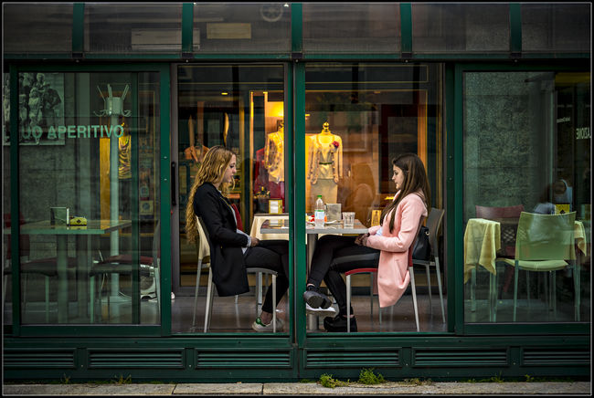 Confession Bar Bistrot Blonde Chair Clothes Coffee Bar Confession Friends Girl Intimacy Lifestyles Open Person Restaurant Sitting Sliding Door Street Streetphotography Table Veranda Window People And Places.