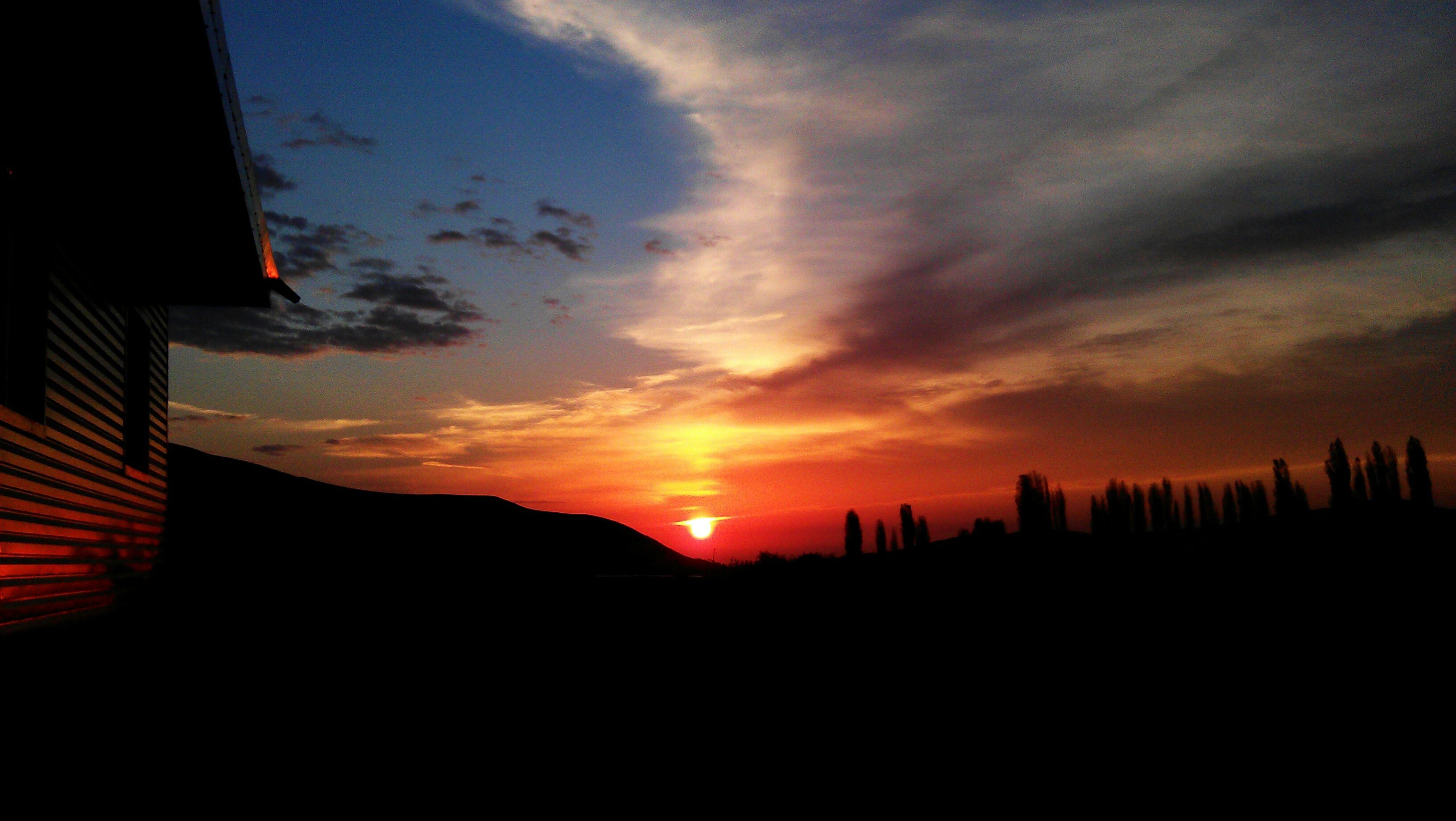 sunset, silhouette, orange color, sun, sky, scenics, beauty in nature, tranquil scene, cloud - sky, idyllic, tranquility, built structure, building exterior, nature, dramatic sky, dark, architecture, sunlight, landscape, cloud