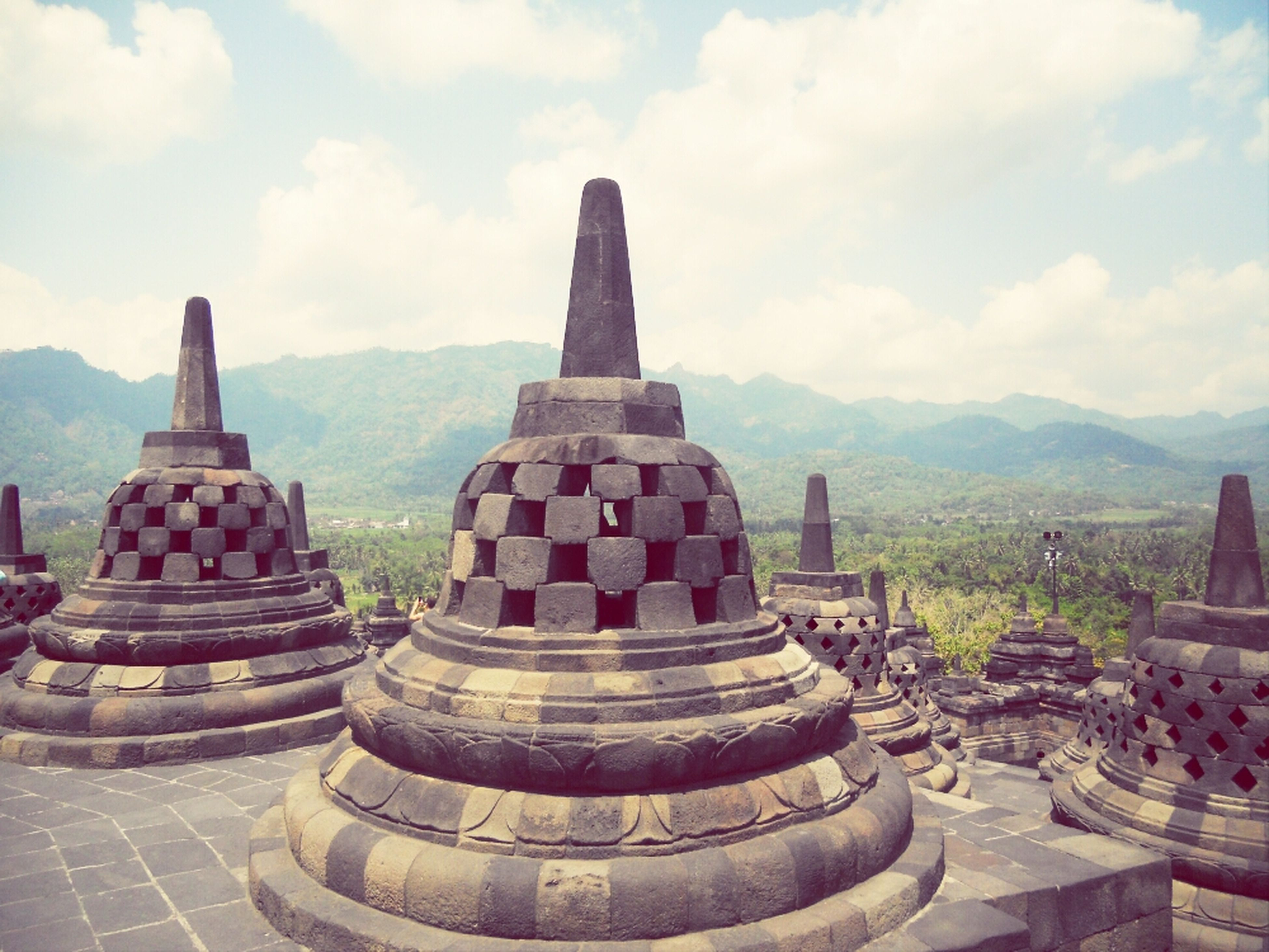 religion, sky, spirituality, temple - building, famous place, travel destinations, mountain, place of worship, tourism, stupa, ancient, culture, travel, history, ancient civilization, cloud - sky, cultures, tranquility, stone material