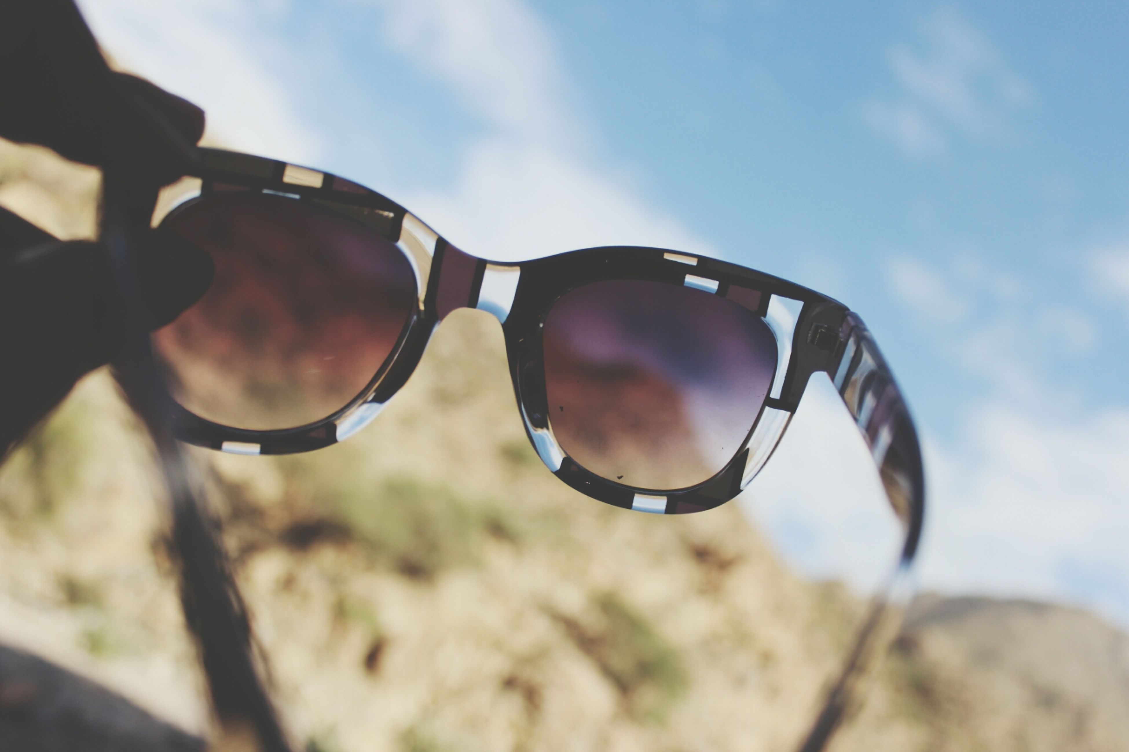 sky, focus on foreground, close-up, cloud - sky, cloud, day, sunglasses, part of, outdoors, leisure activity, reflection, low angle view, selective focus, sunlight, cropped, nature, circle, person