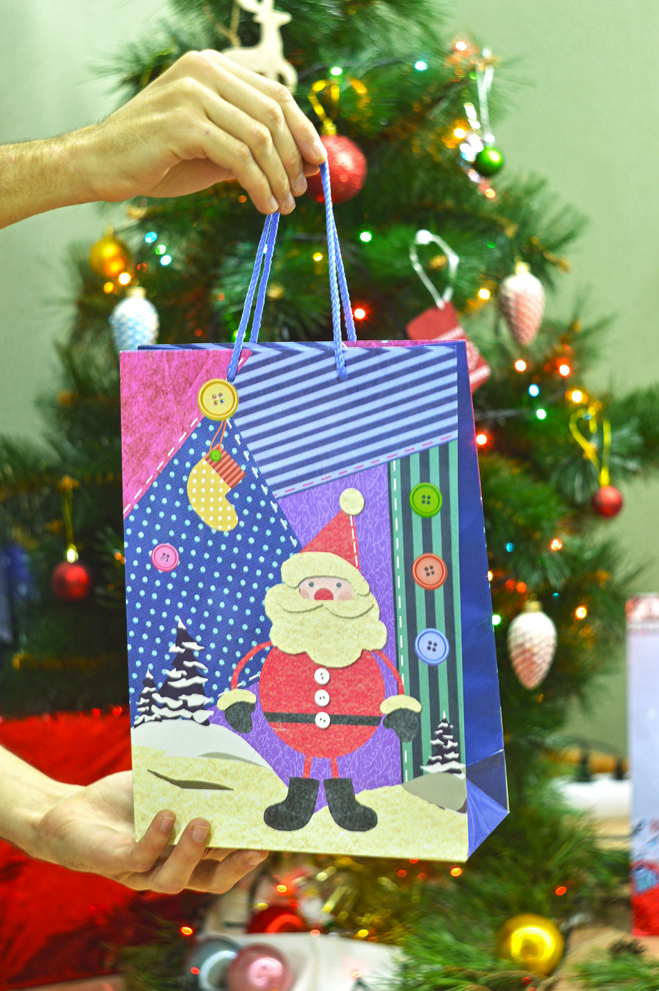 Man holding gift bag on background decorated balls Christmas tree Celebration Child Childhood Children Only Christmas Christmas Decoration Christmas Lights Christmas Ornament Christmas Present Christmas Tree Close-up Day Focus On Foreground Gift Holiday - Event Indoors  One Person People Tradition Tree