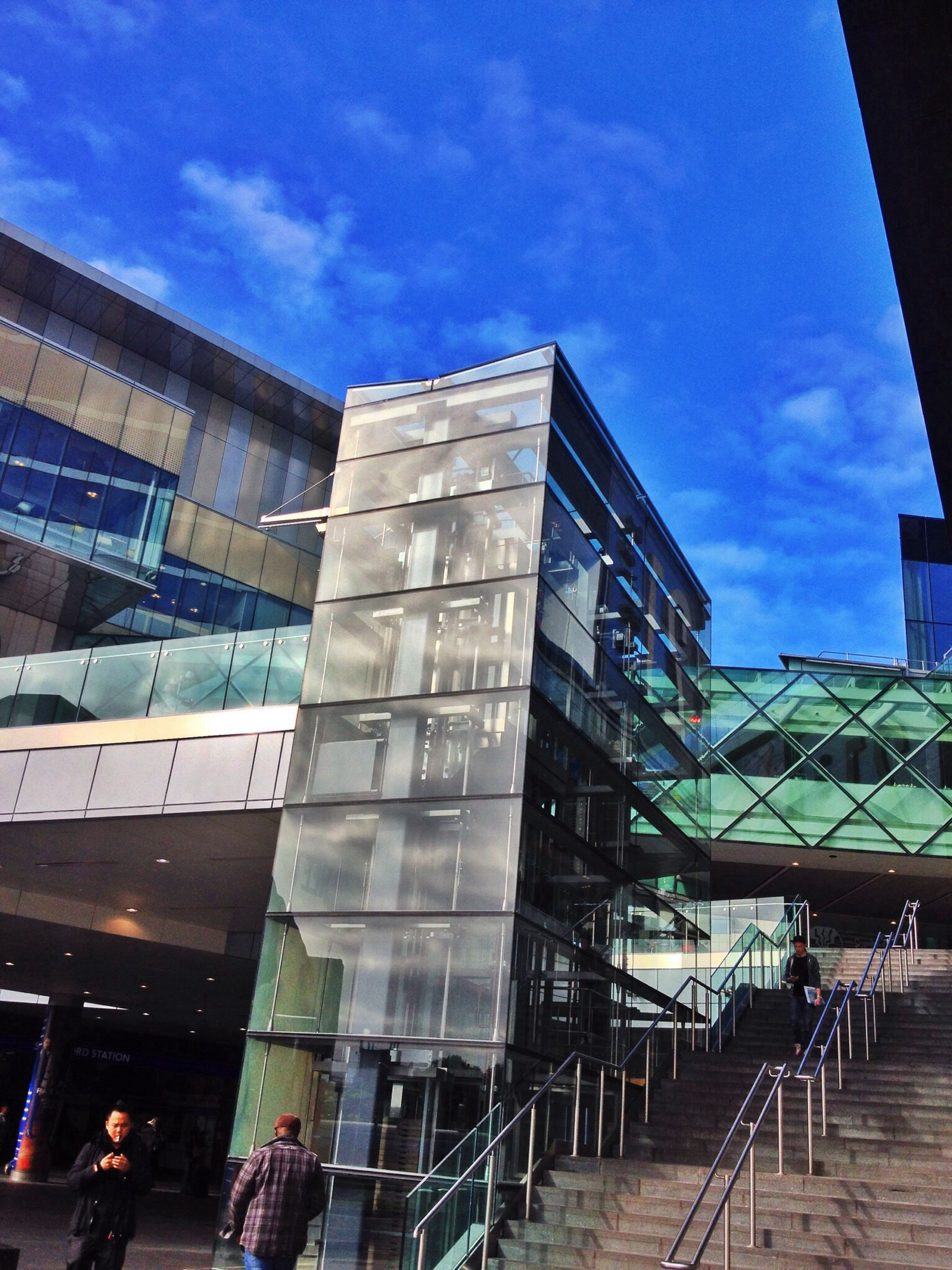 architecture, building exterior, built structure, low angle view, city, building, sky, modern, window, glass - material, reflection, office building, city life, sunlight, day, outdoors, blue, residential building, no people, cloud - sky