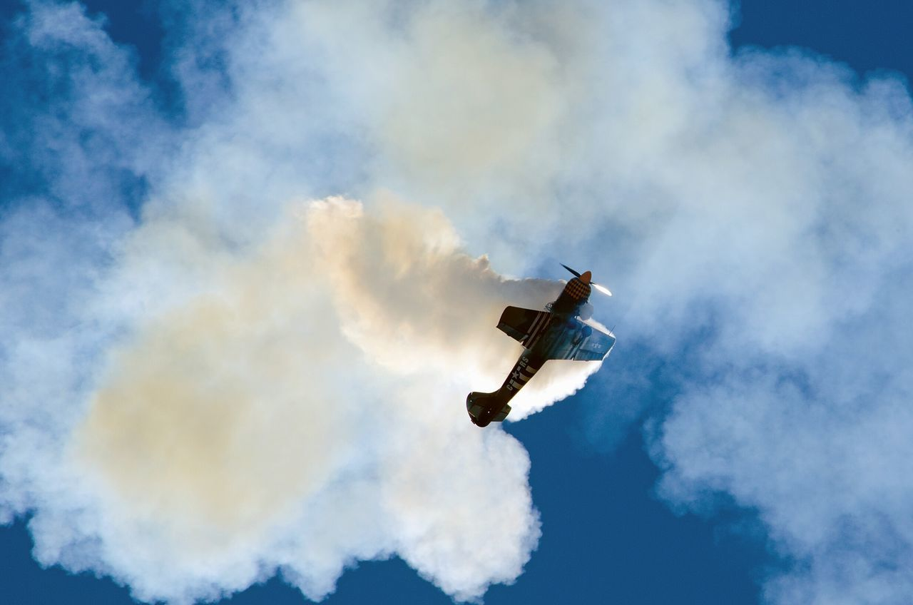 low angle view, sky, cloud - sky, smoke - physical structure, mid-air, flying, air vehicle, airplane, day, outdoors, transportation, airshow, blue, military airplane, no people, fighter plane, vapor trail