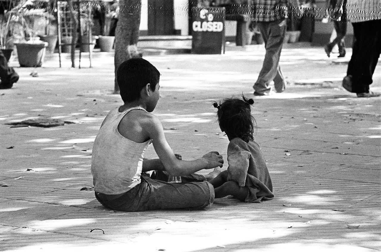 real people, sitting, boys, childhood, crouching, full length, day, outdoors, men, lifestyles, two people, togetherness, mammal, adult, people