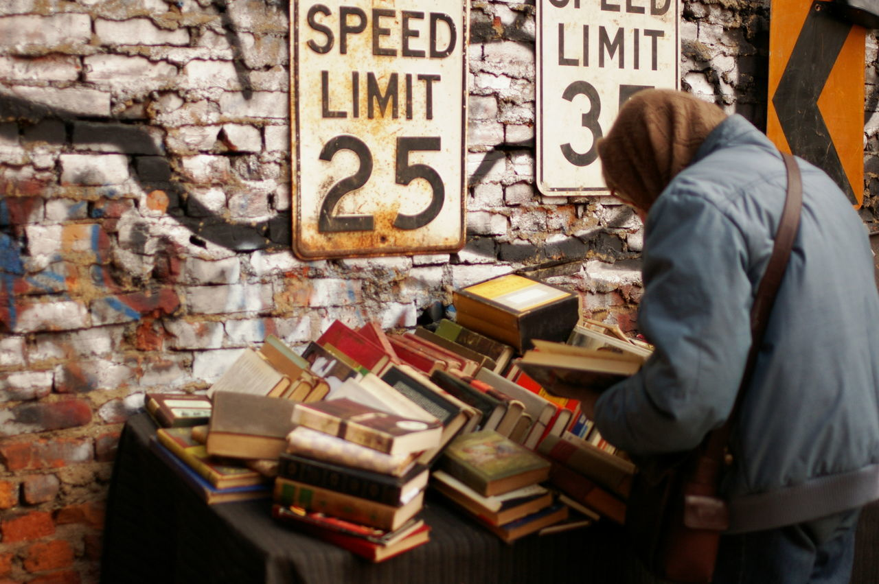 Books Brick Wall Browsing City Day Fleamarket Old Books One Person Outdoors People Speed Limit Sign Woman