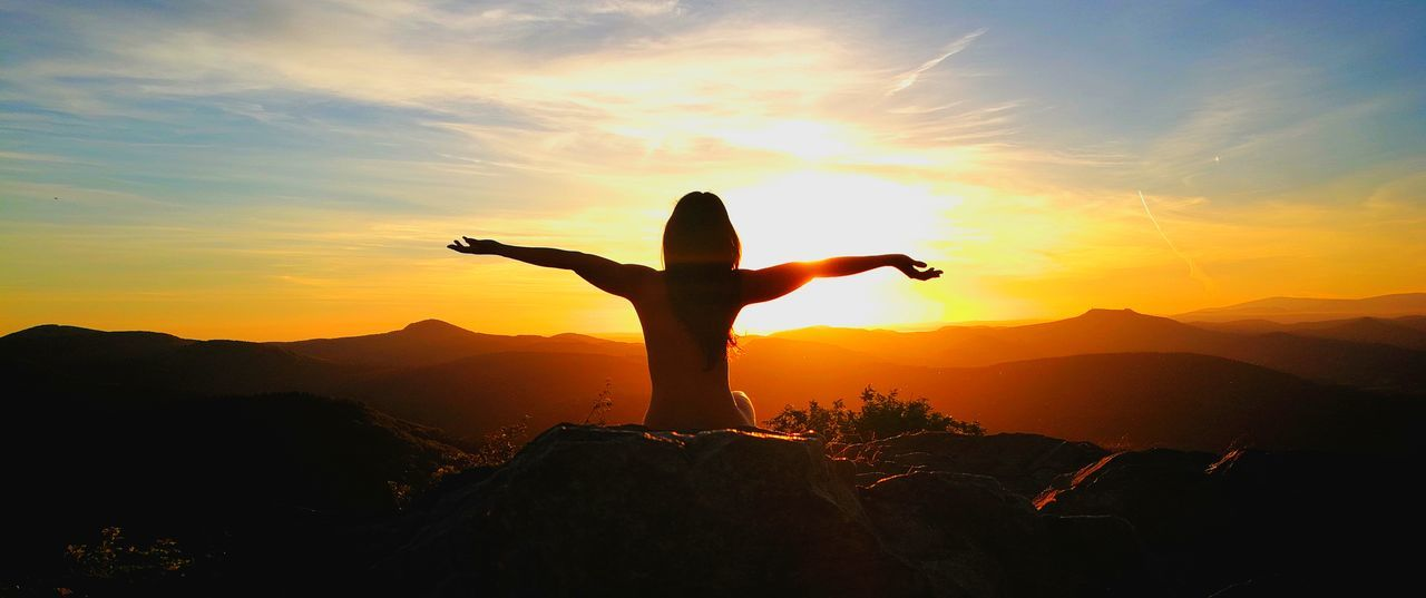 sunset, mountain, silhouette, sky, arms outstretched, arms raised, real people, nature, beauty in nature, scenics, one person, leisure activity, outdoors, mountain range, cloud - sky, lifestyles, standing, human hand, men, women, adventure, young women, young adult, energetic, day, people