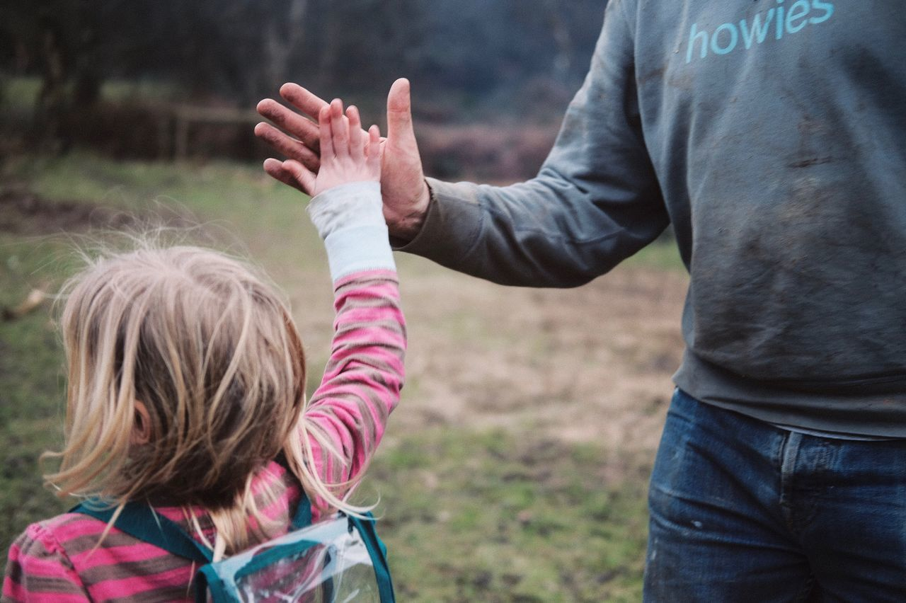 People Two People Real People Rear View Focus On Foreground Casual Clothing Bonding Outdoors Leisure Activity Day Togetherness Human Hand Childhood Men Warm Clothing Human Body Part Nature Close-up Community Outreach Nature Young Women Lifestyles Grass Celebration Highfive