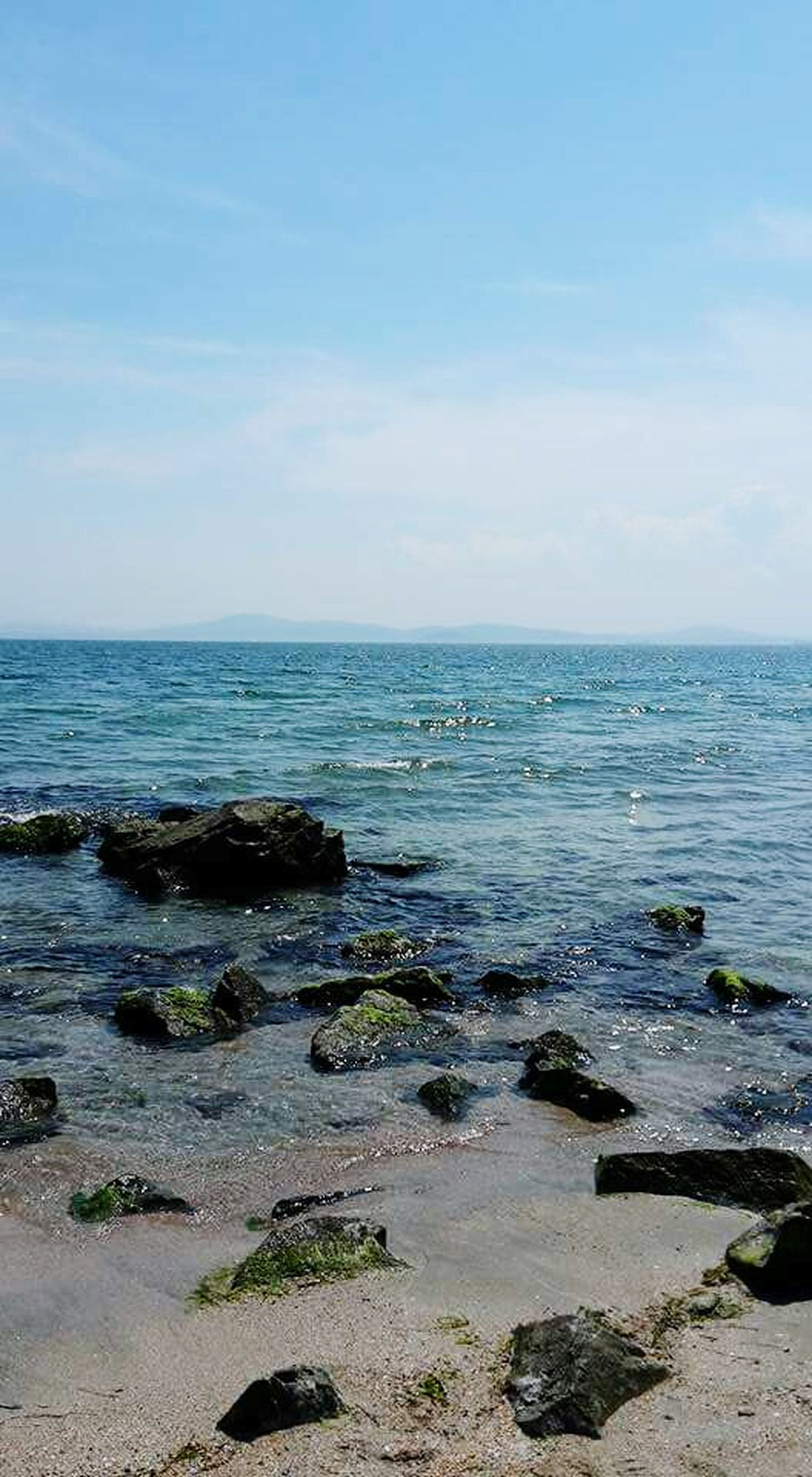 sea, water, horizon over water, tranquil scene, scenics, tranquility, beauty in nature, blue, sky, beach, nature, rock - object, shore, idyllic, rippled, day, wave, outdoors, seascape, no people
