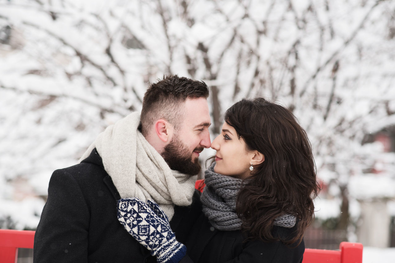 couple looking at each other Adult Adults Only Bonding Cold Temperature Couple - Relationship Embracing Happiness Heterosexual Couple Knit Hat Lifestyles Love Men People Romance Smiling Snow Sweater Togetherness Two People Valentine's Day  Warm Clothing Winter Young Adult Young Men Young Women