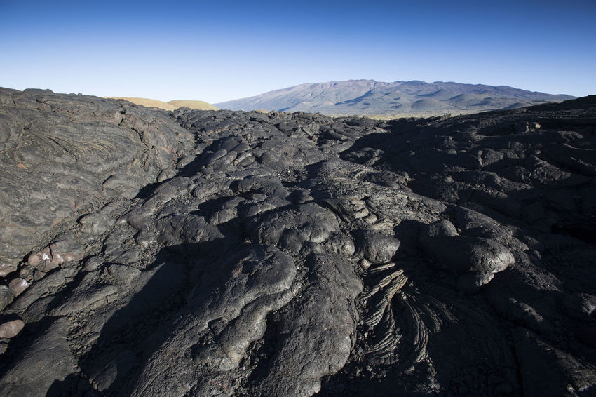 Cold Lava flow in the near of volcano Mauna Kea Lava Flow Mauna Kea Arid Climate Beauty In Nature Black Rocks Clear Sky Day Geology Landscape Lava Mountain Mountain Range Nature No People Outdoors Physical Geography Rock - Object Rock Formation Scenics Sky Tranquil Scene Tranquility Travel Destinations Volcanic Landscape Volcano