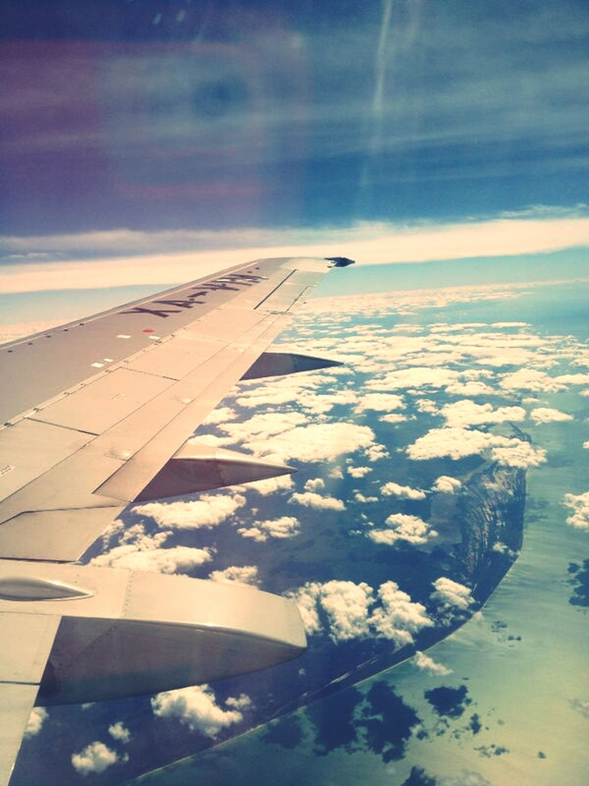 flying, aircraft wing, airplane, transportation, sky, aerial view, air vehicle, part of, cropped, scenics, beauty in nature, cloud - sky, landscape, travel, nature, mode of transport, tranquil scene, tranquility, mid-air, blue