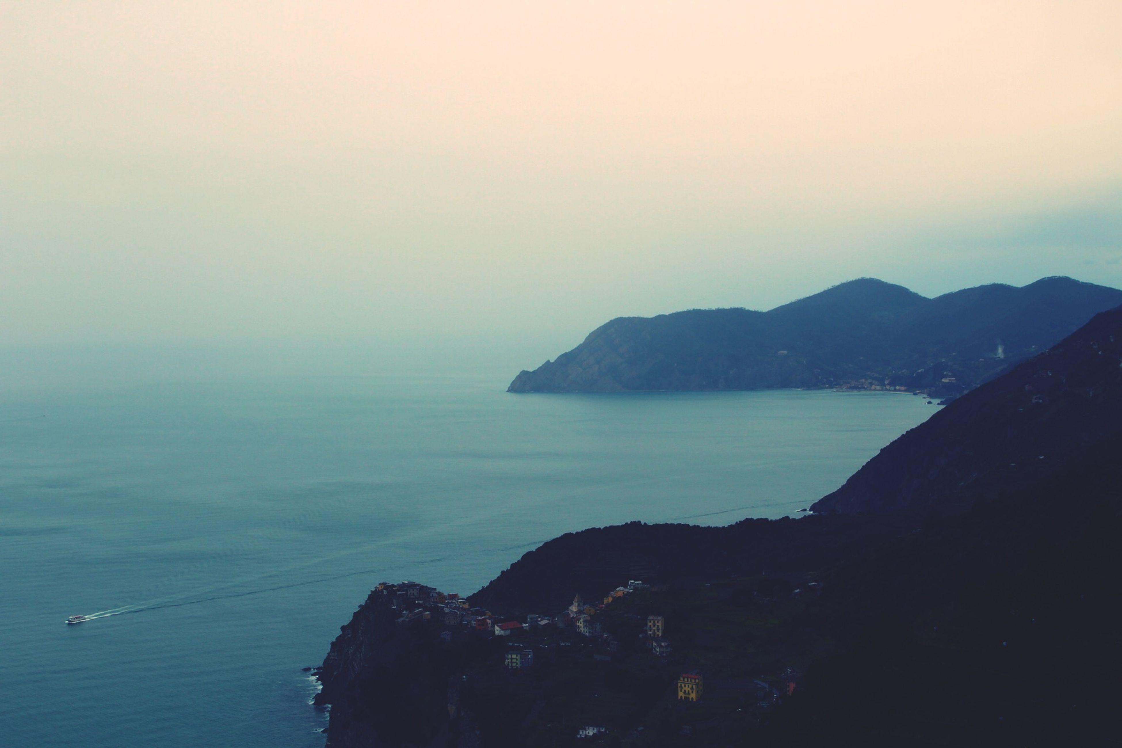Rocks and calm blue sea against clear sky