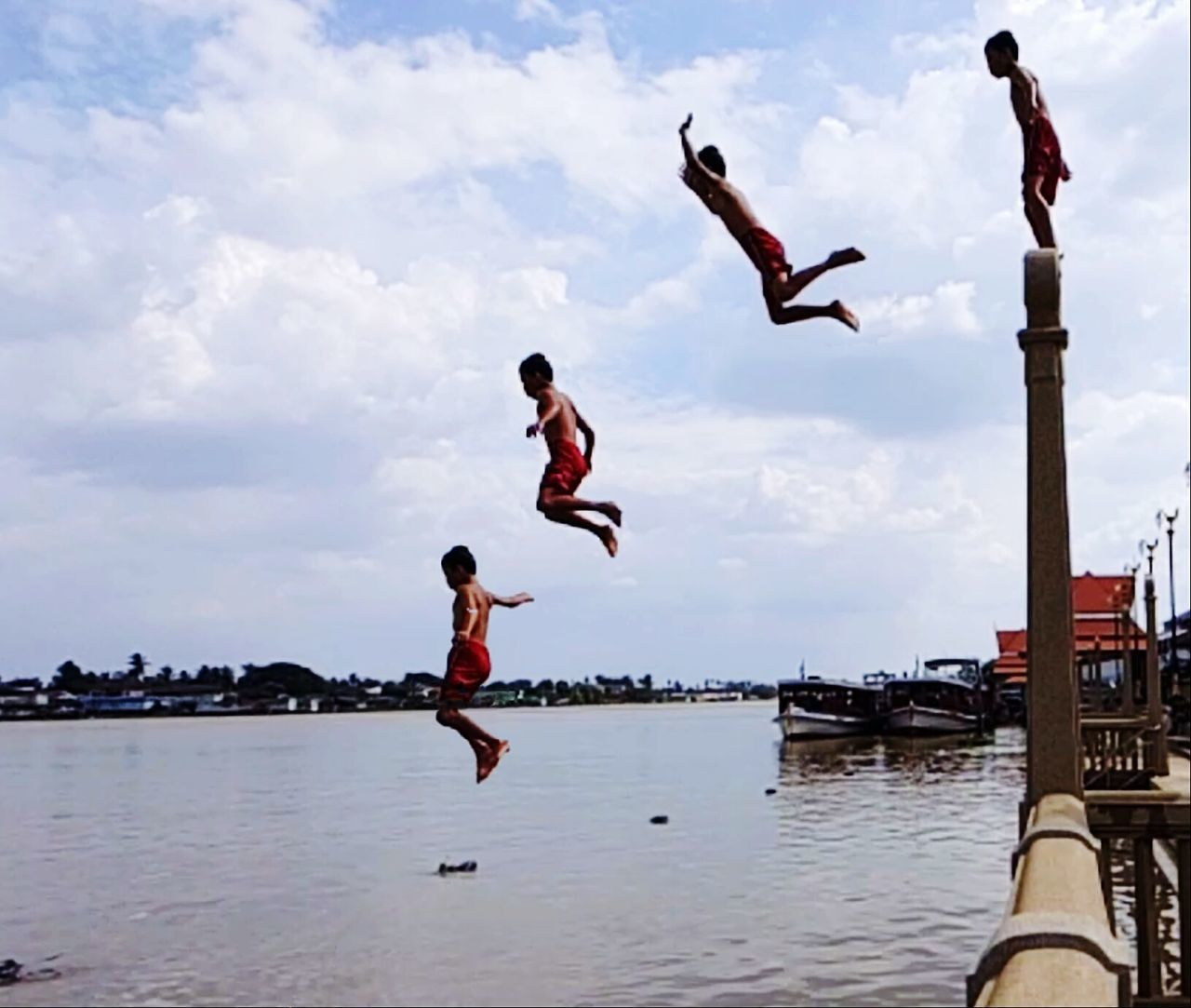 real people, mid-air, water, jumping, leisure activity, sky, lifestyles, men, full length, cloud - sky, day, outdoors, fun, enjoyment, motion, nature, vacations, skill, sea, large group of people, women, handstand, stunt, energetic, people