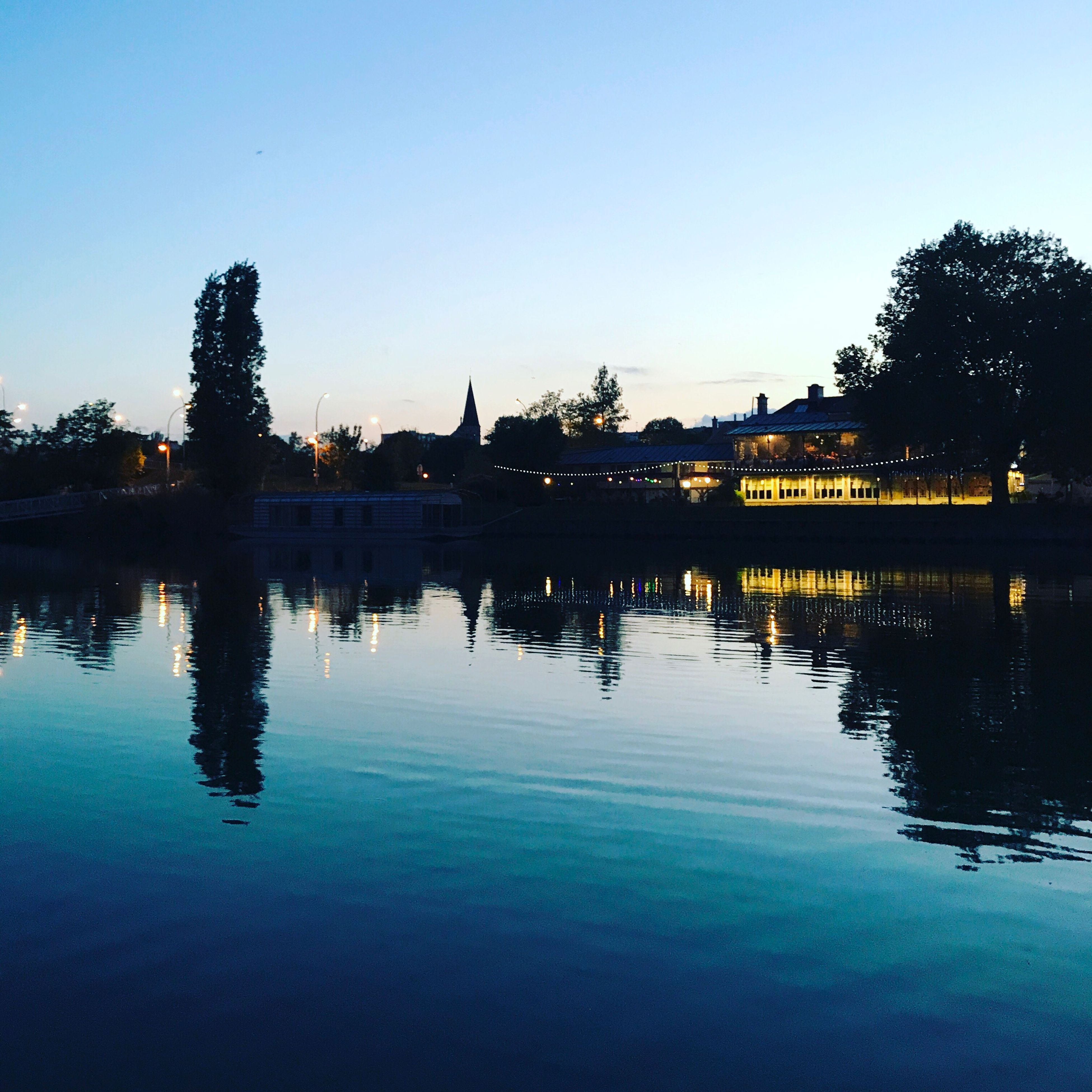 water, reflection, silhouette, tree, sunset, built structure, lake, waterfront, architecture, outdoors, blue, sky, building exterior, clear sky, tranquil scene, nature, scenics, swimming pool, beauty in nature, no people, city, day