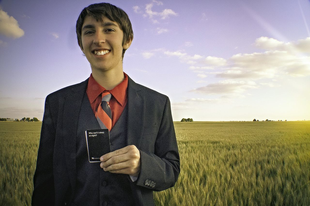 field, one person, waist up, portrait, looking at camera, smiling, growth, young adult, sky, standing, nature, front view, young men, outdoors, agriculture, real people, rural scene, day, suit, happiness, businessman, landscape, lifestyles, men, beauty in nature, well-dressed, people