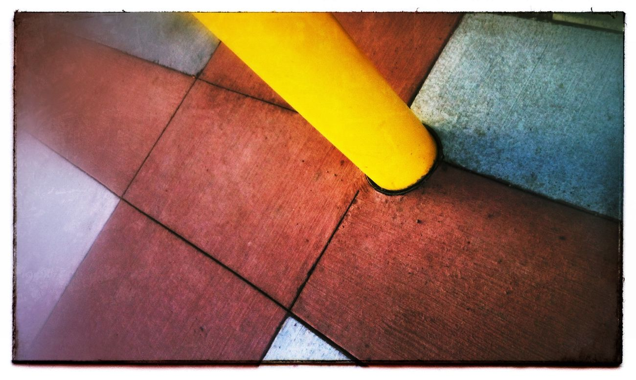 Yellow pole, red pavement. Photography IPhone Colours Abstract