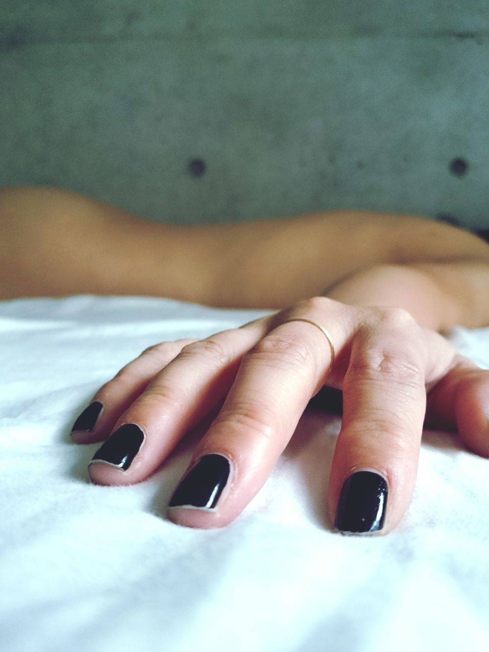 Cropped Hand Woman With Black Nail Polish On Bed At Home