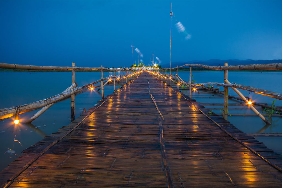 PHAYAO, THAILAND - JULY 19, 2016: The bamboo bridge, The bamboo bridge of Wat Ti Lok Aram temple in kwan phayao off freshwater lake of Thailand. Day is the important Buddhist. ASIA Bamboo Bridge Beauty In Nature Blue Buddhist Diminishing Perspective Engineering Illuminated Important Kwan Phayao Nature Night No People Outdoors Scenics Sky Temple Thailand The Way Forward Tranquil Scene Tranquility Travel Destinations Vanishing Point Wat Ti Lok Aram Water