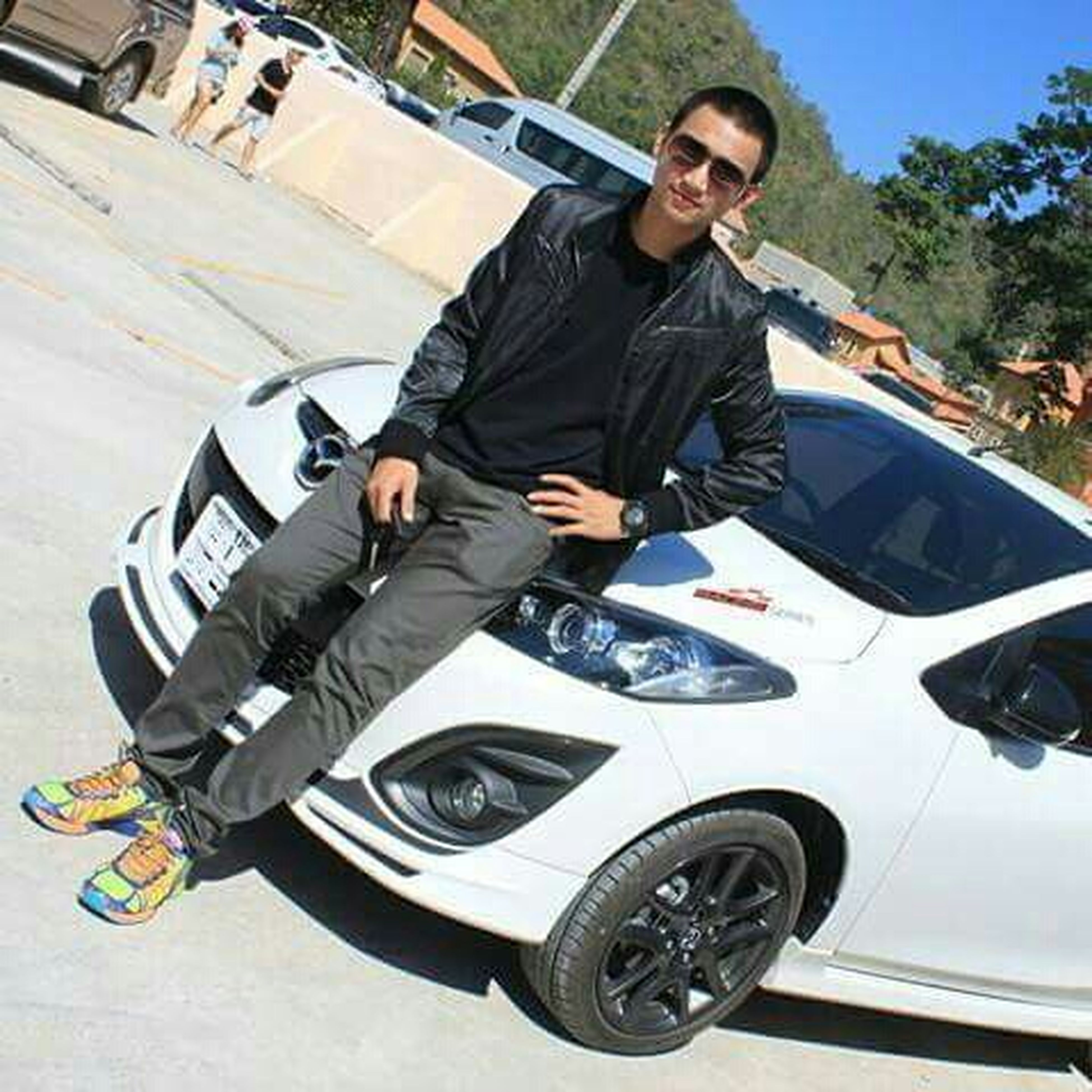lifestyles, young adult, casual clothing, leisure activity, transportation, person, mode of transport, land vehicle, young men, front view, sunglasses, looking at camera, full length, car, portrait, sitting, smiling