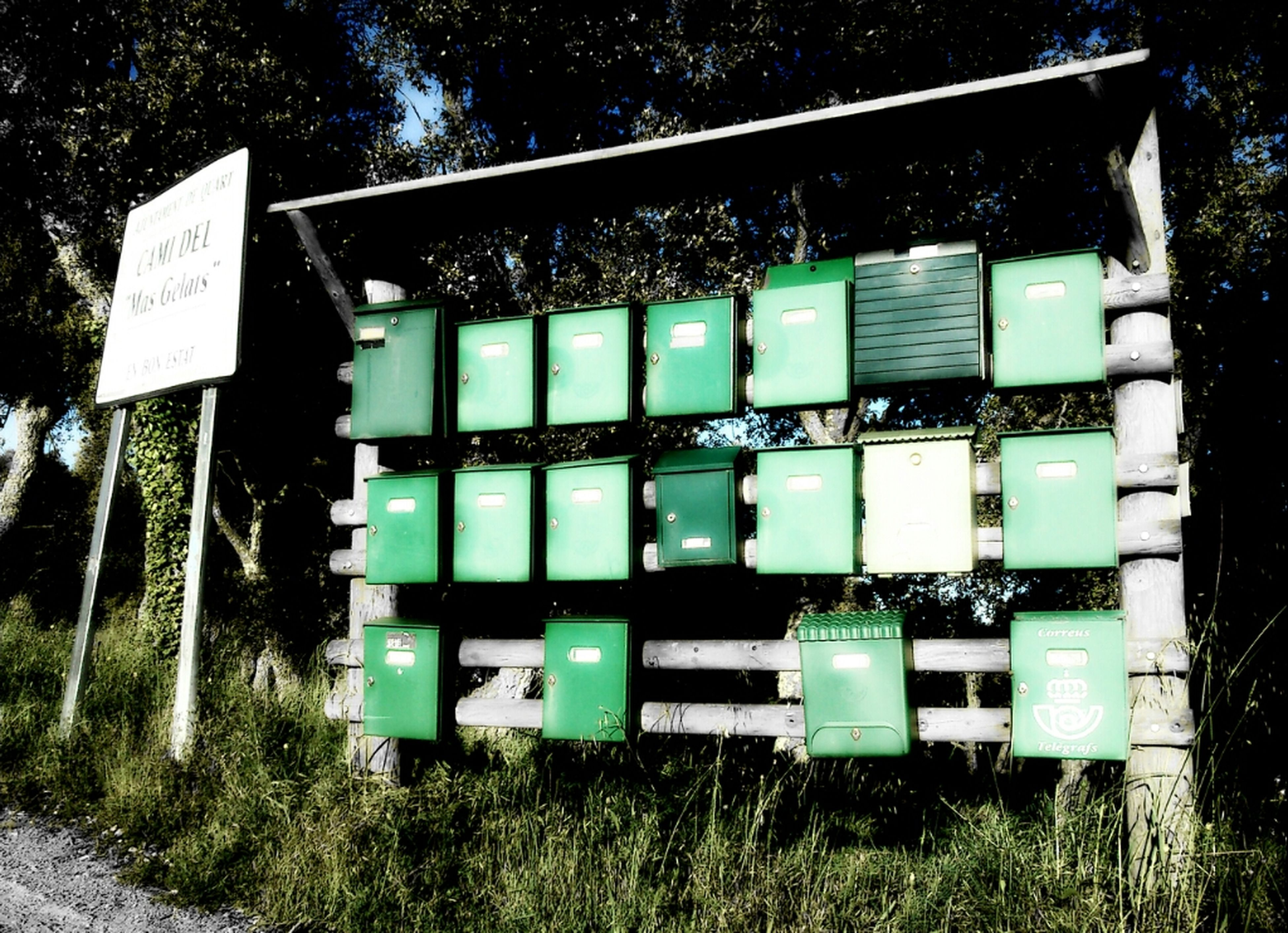 grass, building exterior, built structure, outdoors, architecture, day, no people, field, metal, green color, communication, in a row, western script, tree, text, variation, side by side, abandoned, large group of objects, container