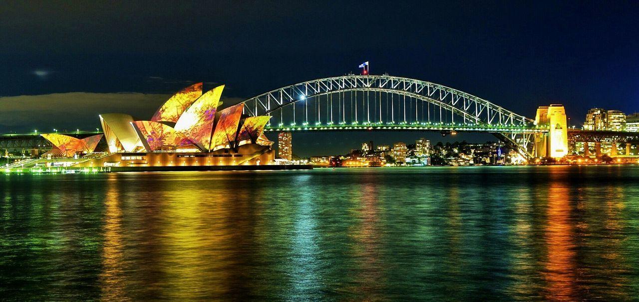 Illuminated Sydney Harbor Bridge And Opera House In City