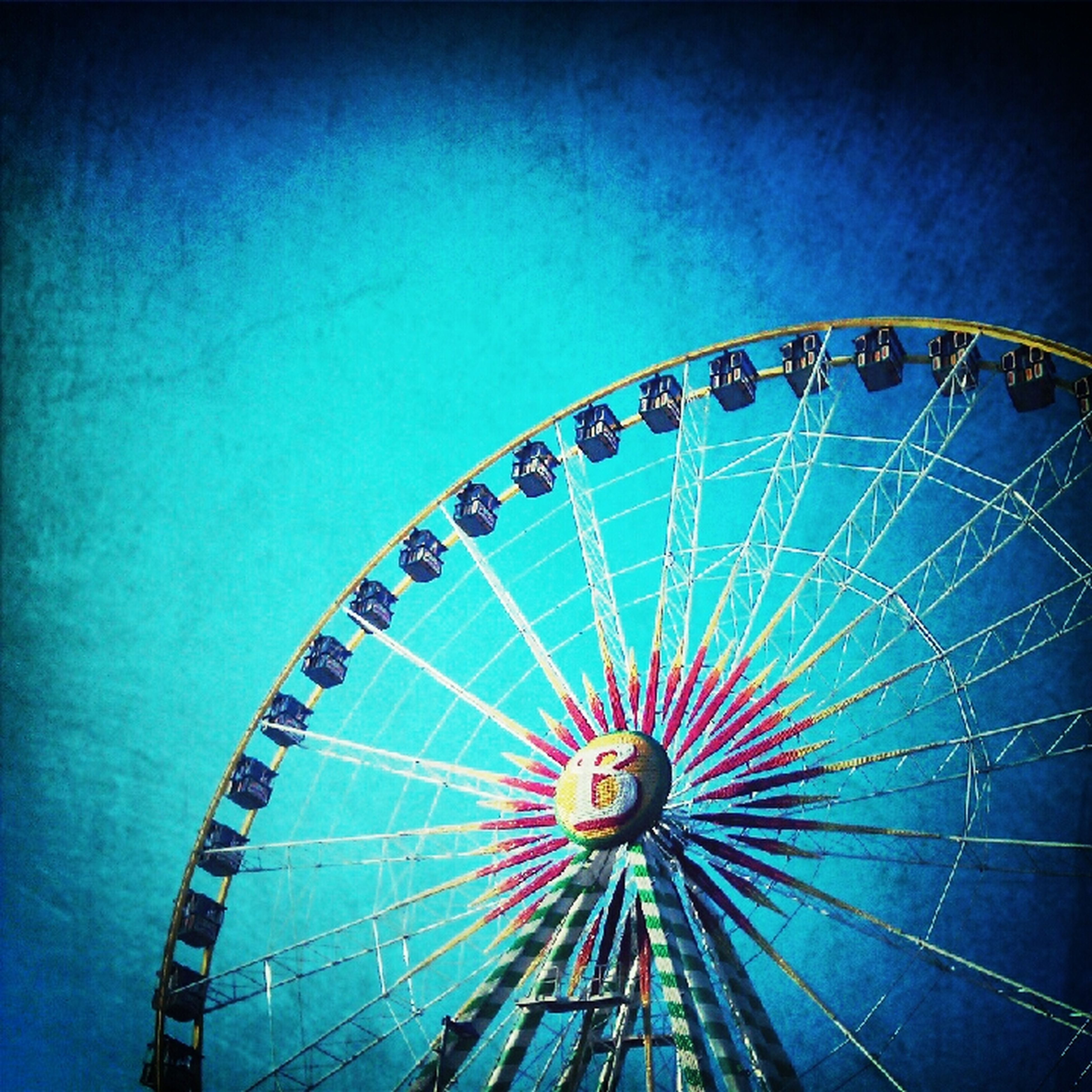 amusement park, ferris wheel, amusement park ride, arts culture and entertainment, low angle view, fun, blue, sky, clear sky, multi colored, enjoyment, leisure activity, circle, big wheel, outdoors, large, fairground, no people, pattern, fairground ride