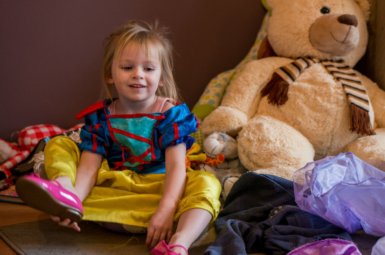 Happy Cute Girl Sitting By Stuffed Toy At Home
