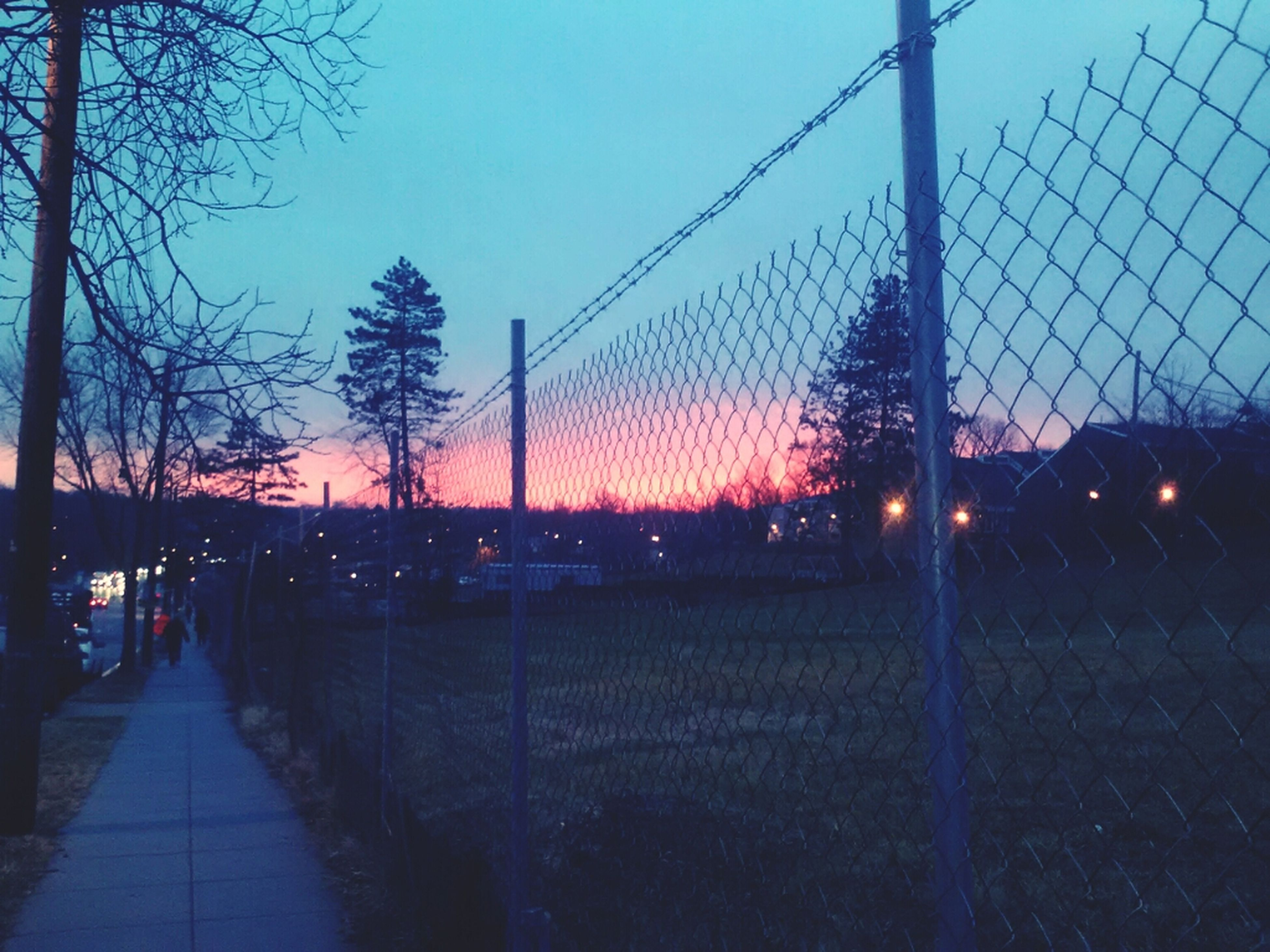 sunset, fence, sky, clear sky, chainlink fence, illuminated, street light, silhouette, protection, built structure, safety, city, dusk, architecture, tree, outdoors, railing, road, connection, metal