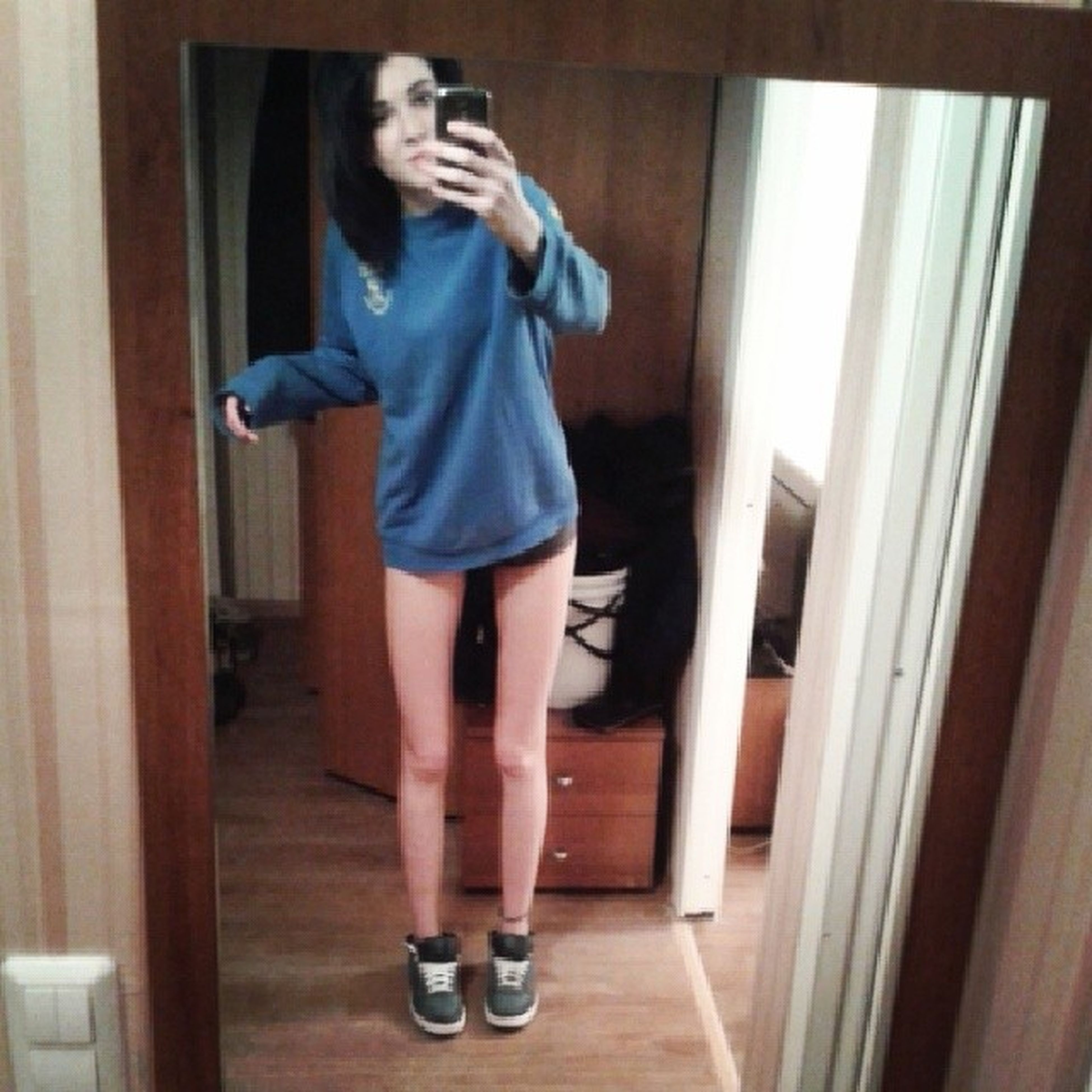 full length, casual clothing, indoors, lifestyles, person, young adult, leisure activity, standing, front view, young women, door, side view, three quarter length, home interior, holding, shorts, childhood