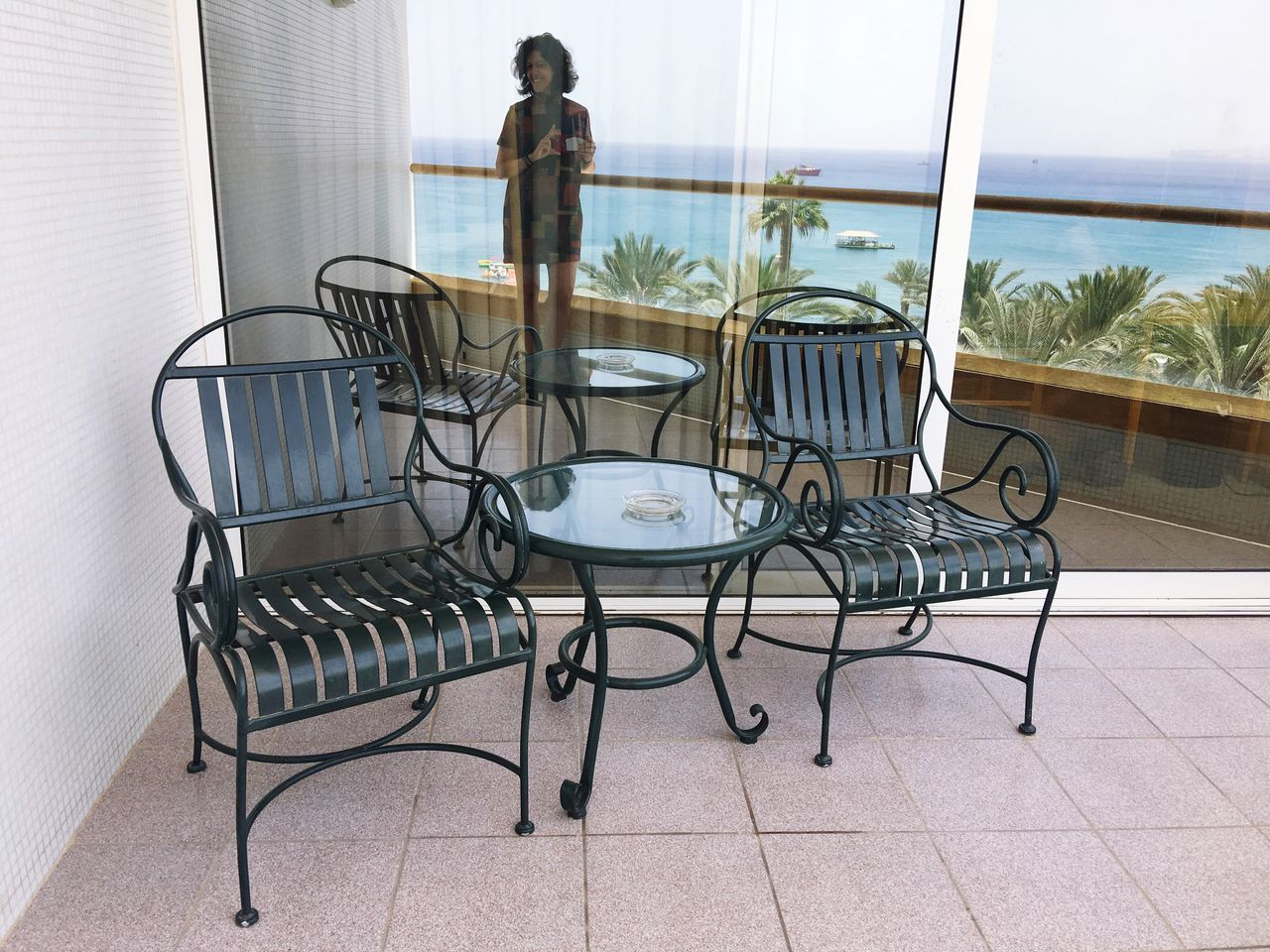 Table Chair Window Hotel View Indoors  One Person People Adult Vacations One Woman Only Lifestyles Standing Sea Reflection Mirrorselfie Mirror Mirror Reflection Women Leisure Activity Summer Water Relaxation Travel Outdoors Porch