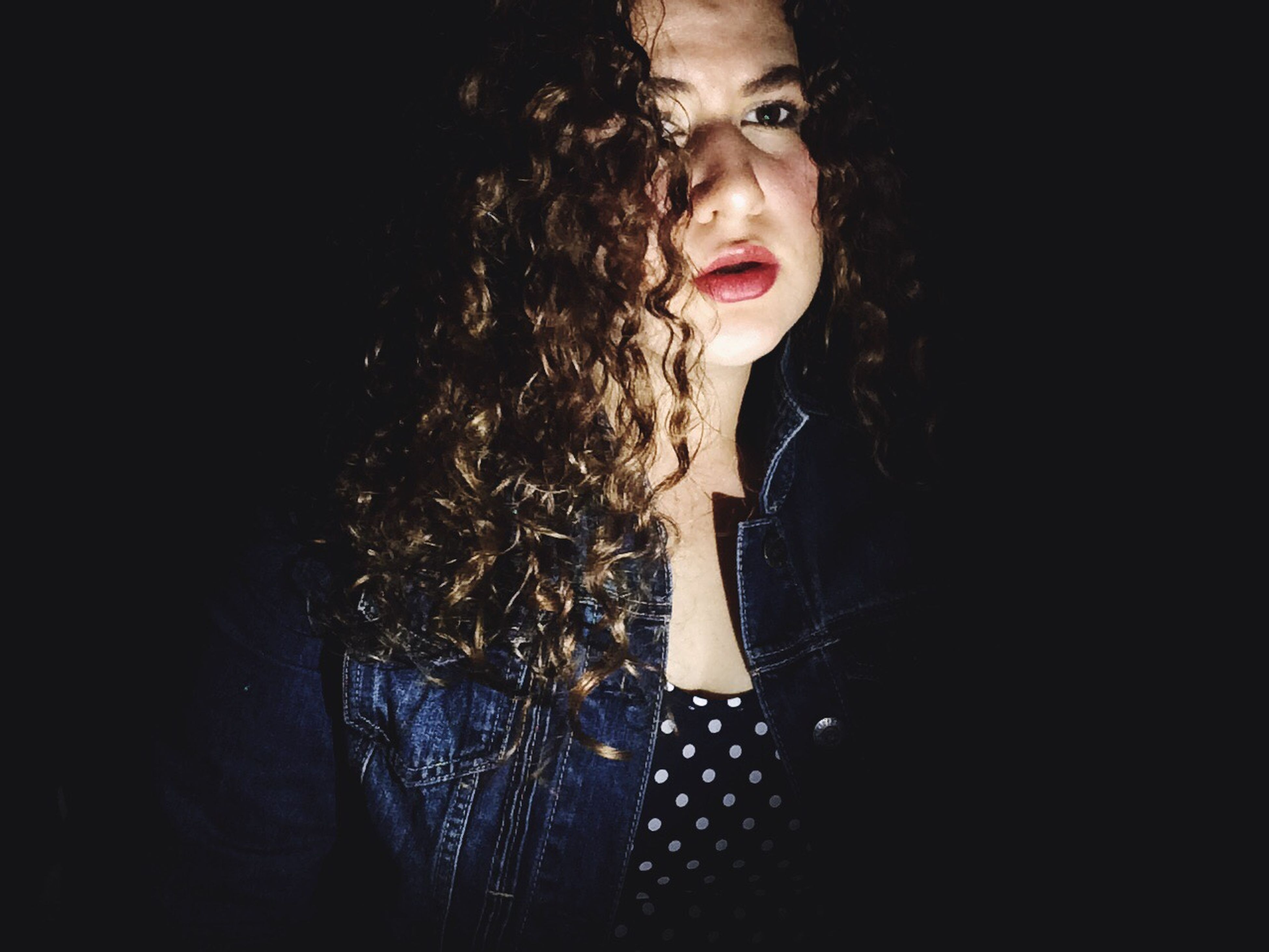one person, adults only, only women, one woman only, headshot, front view, young adult, lipstick, black background, red lipstick, human body part, one young woman only, adult, young women, people, close-up, portrait, night, curly hair, indoors, human lips