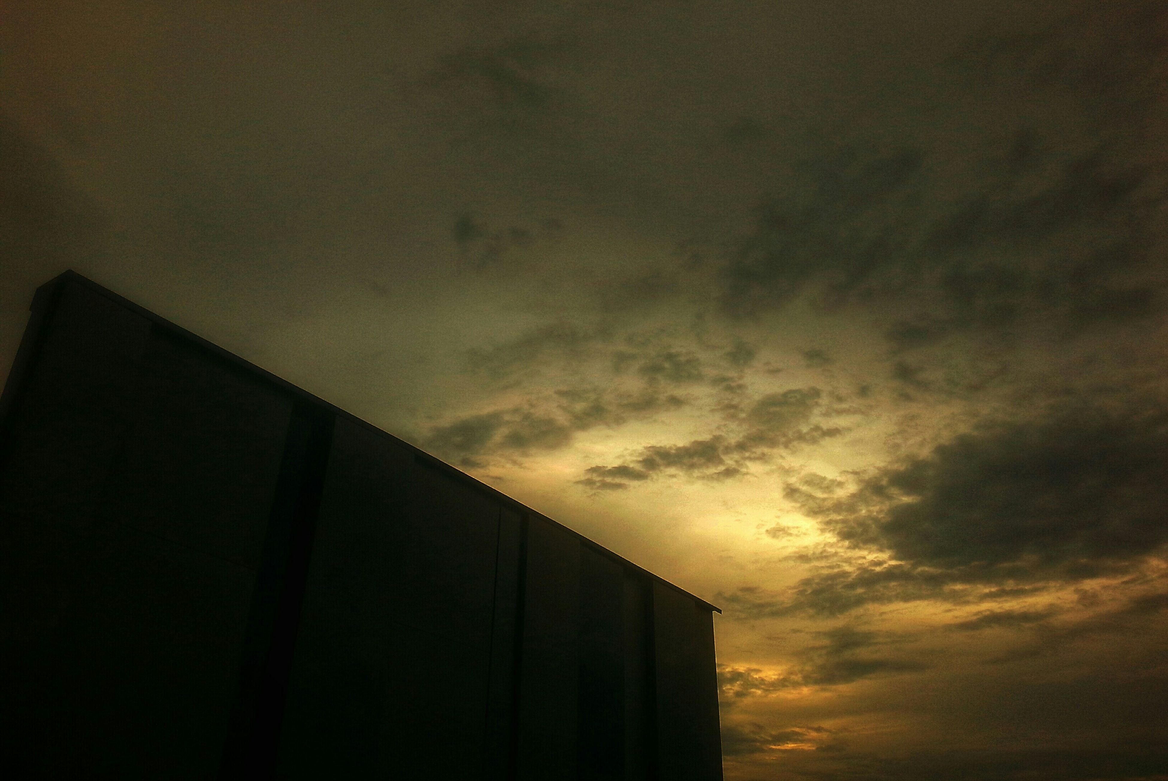 architecture, built structure, building exterior, low angle view, sky, sunset, cloud - sky, building, cloudy, silhouette, high section, cloud, residential structure, city, outdoors, dusk, orange color, residential building, house, no people