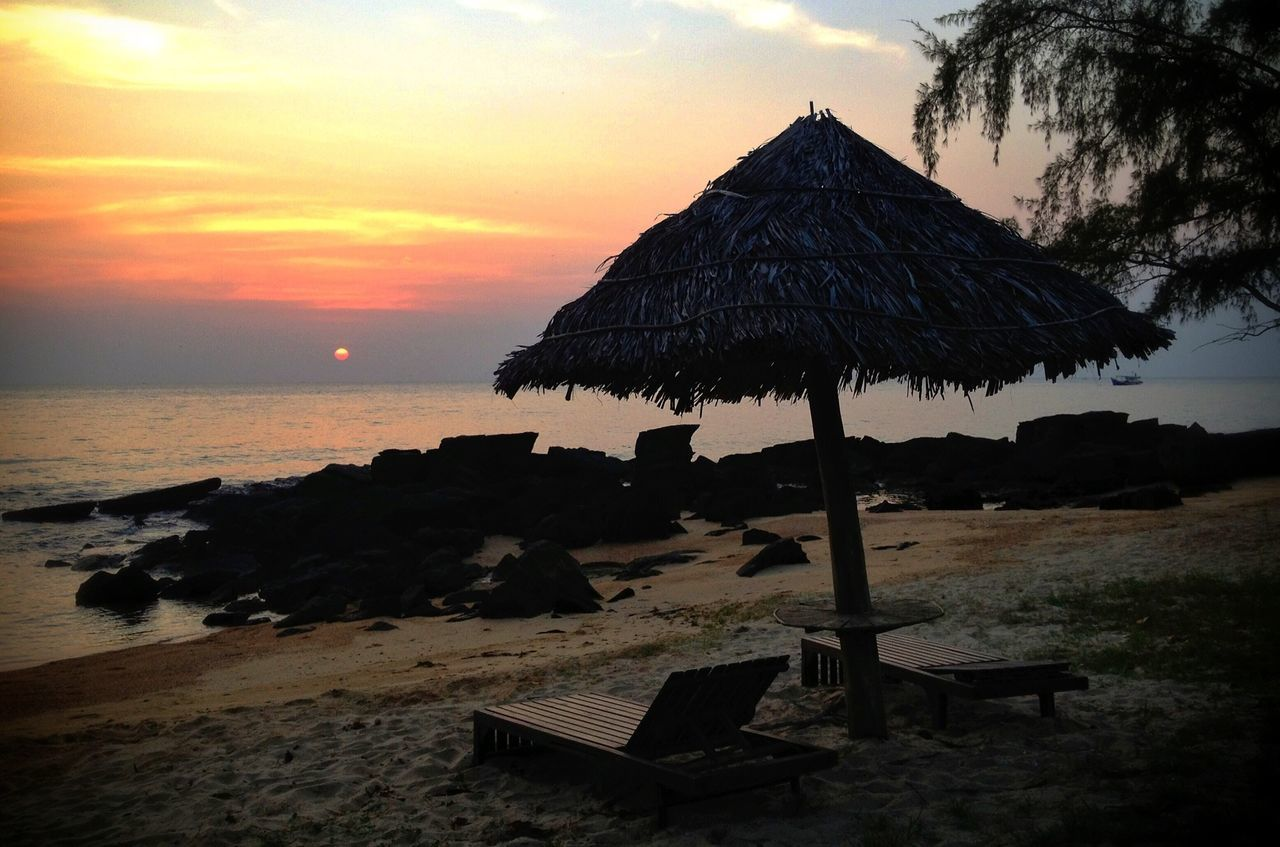 Lounge Chairs And Thatched Roof On Beach At Sunset
