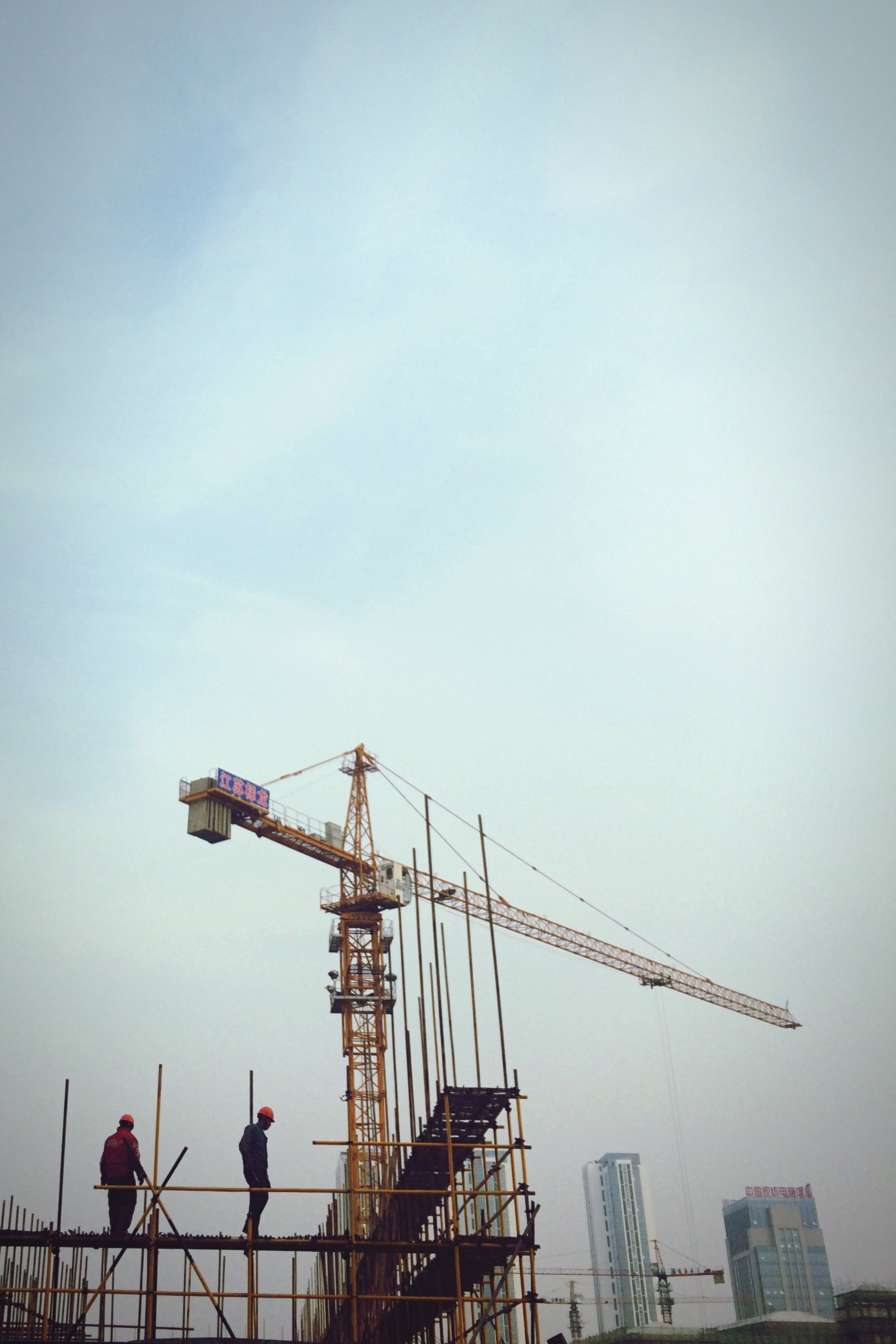 crane - construction machinery, construction site, development, crane, built structure, architecture, building exterior, construction, industry, construction industry, low angle view, incomplete, sky, progress, clear sky, tall - high, city, copy space, commercial dock, outdoors