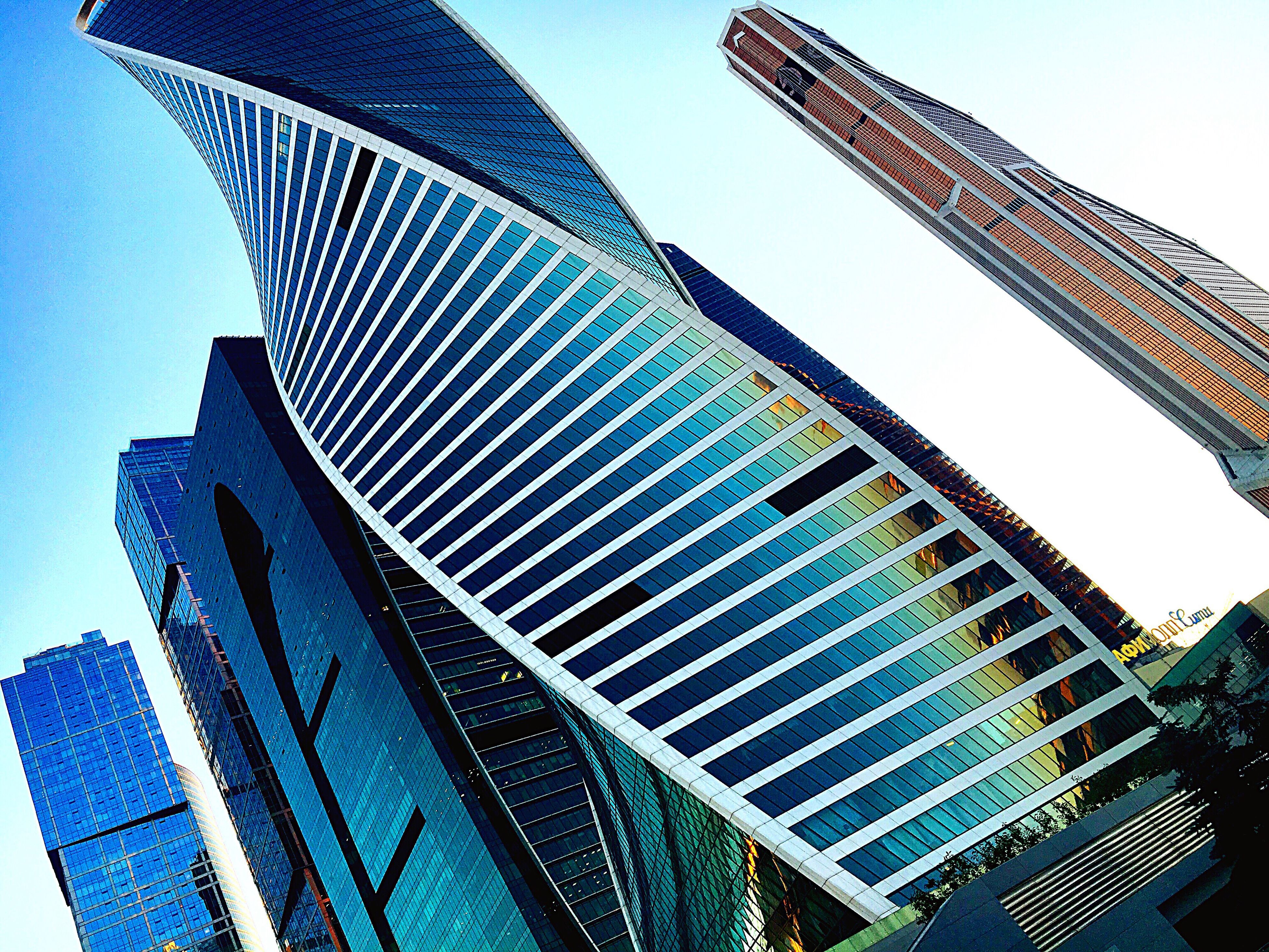 low angle view, architecture, building exterior, built structure, clear sky, skyscraper, tower, office building, city, tall - high, modern, sky, tall, place of work, blue, building story, outdoors, repetition, development, day, financial district, architectural feature, city life, no people, capital cities, urban skyline