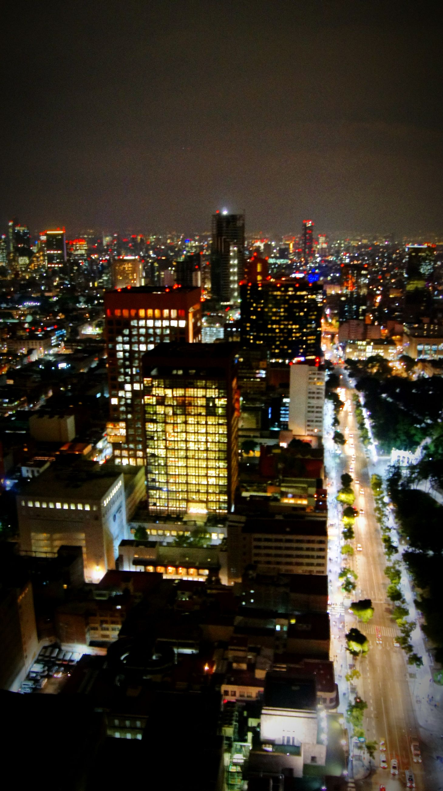 city, illuminated, building exterior, cityscape, night, architecture, skyscraper, city life, urban skyline, built structure, modern, outdoors, travel destinations, downtown district, no people, office building exterior, sky