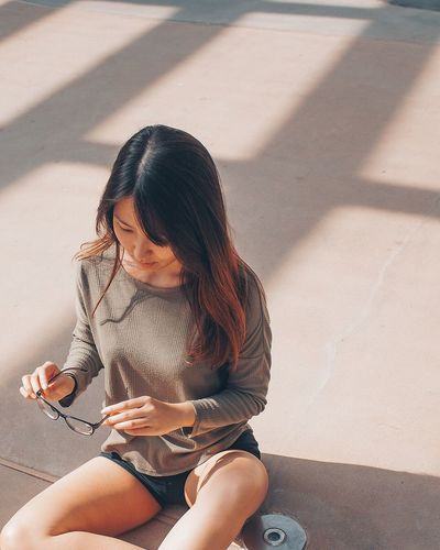 Sitting High Angle View Three Quarter Length One Person Wireless Technology Day Technology Outdoors Shadow Sunlight Real People Portable Information Device Communication Mobile Phone Women Young Women Young Adult Lifestyles Road Leisure Activity EyeEm Ready