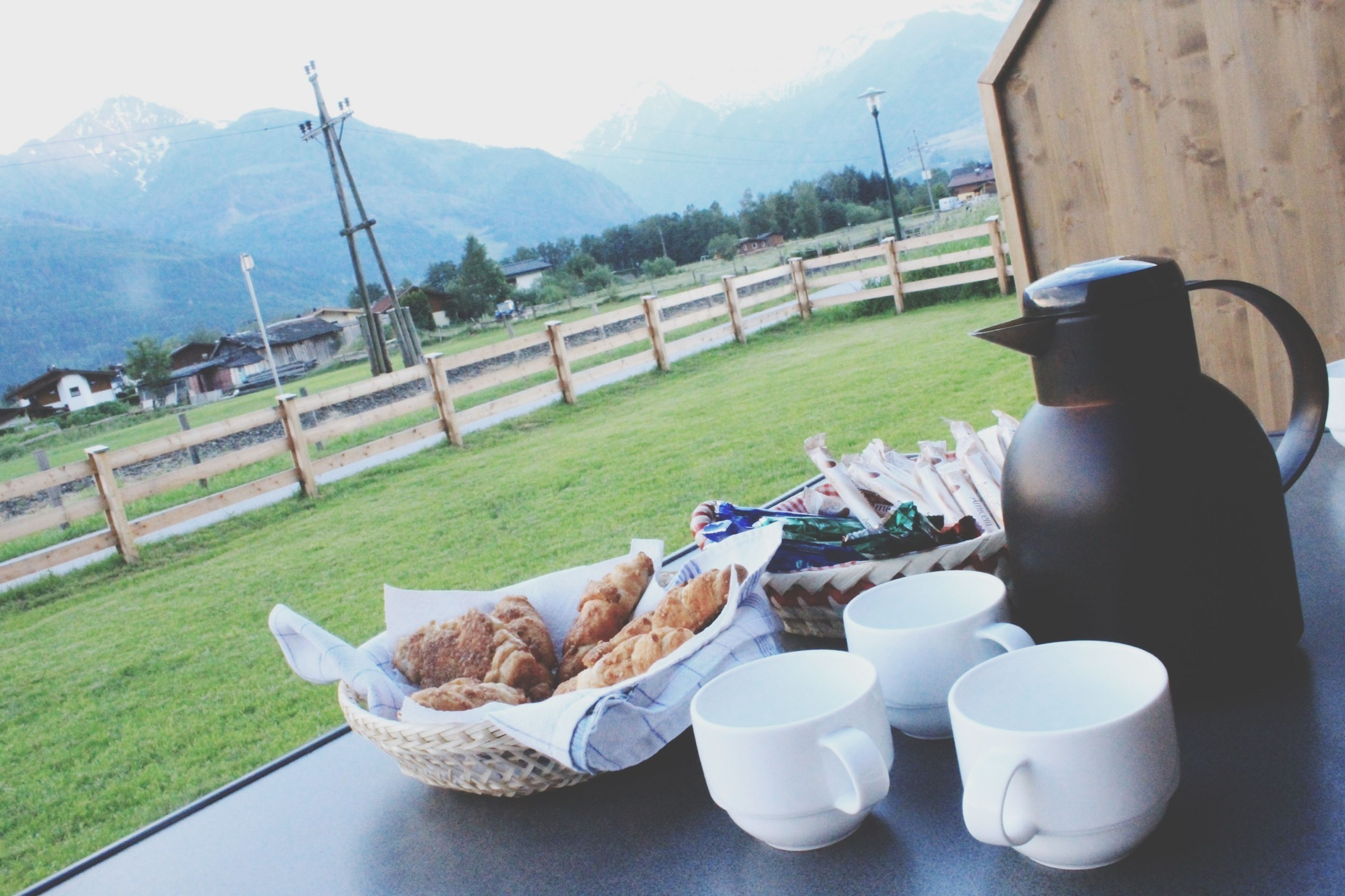mountain, mountain range, grass, landscape, food and drink, sky, tranquility, table, tranquil scene, nature, day, scenics, sunlight, green color, outdoors, food, beauty in nature, field, tree, relaxation