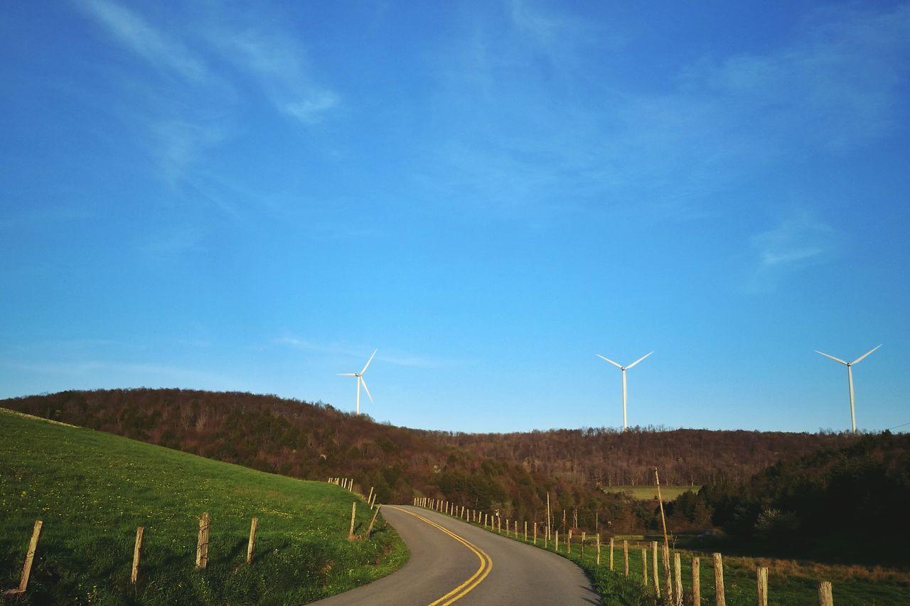 Road By Windmills On Field Against Blue Sky