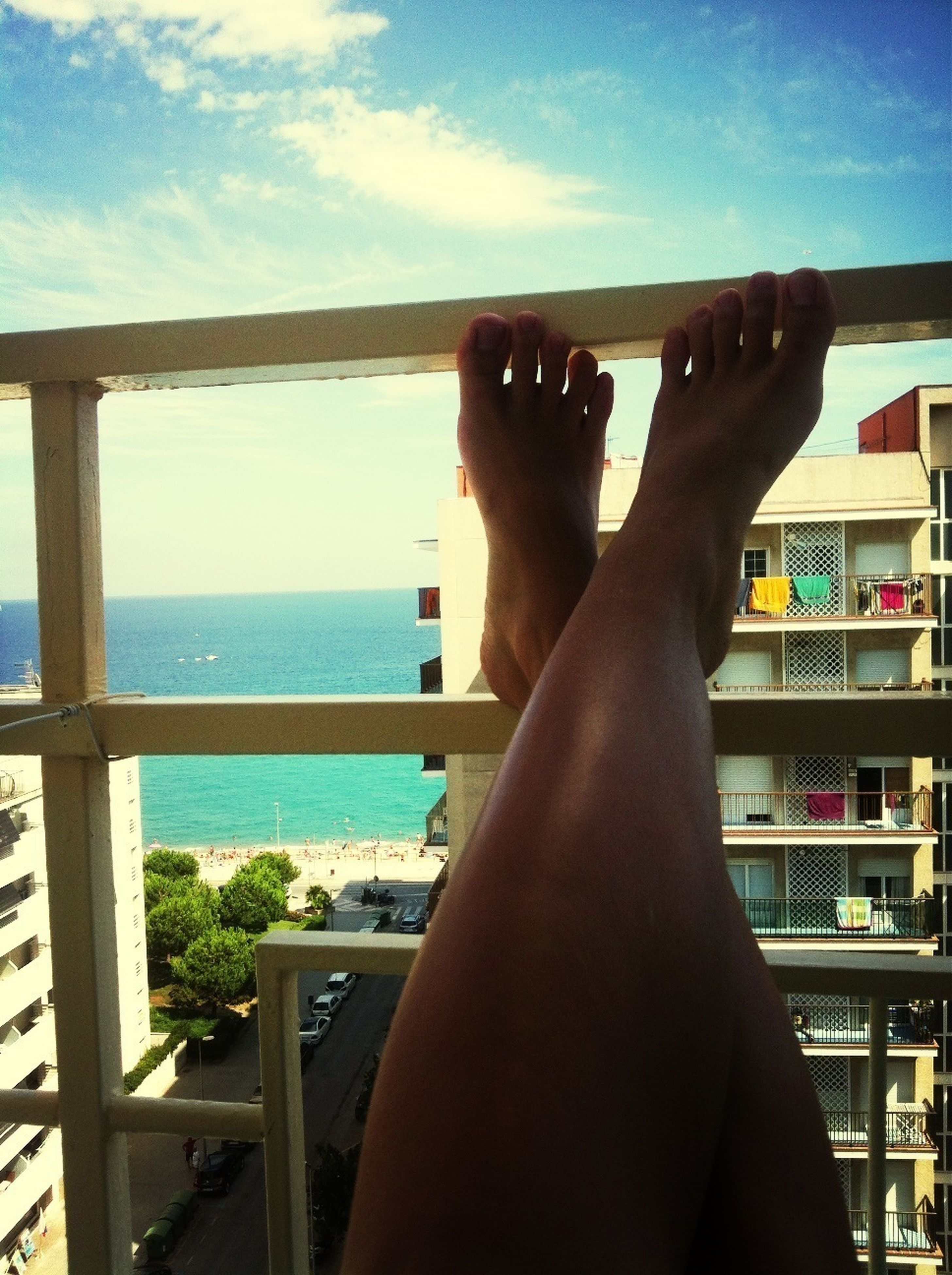 person, barefoot, relaxation, low section, lifestyles, sea, sky, leisure activity, indoors, personal perspective, sunlight, legs crossed at ankle, horizon over water, railing, water, window
